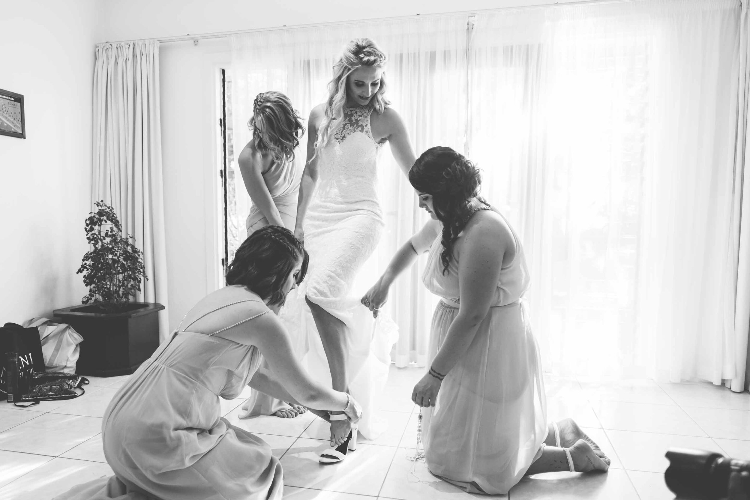 the bridesmaids helping the bride into her heels