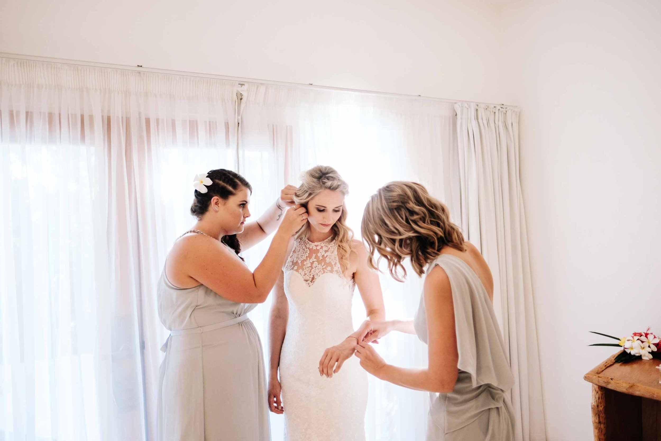 the bridesmaids helping the bride with her jewellery