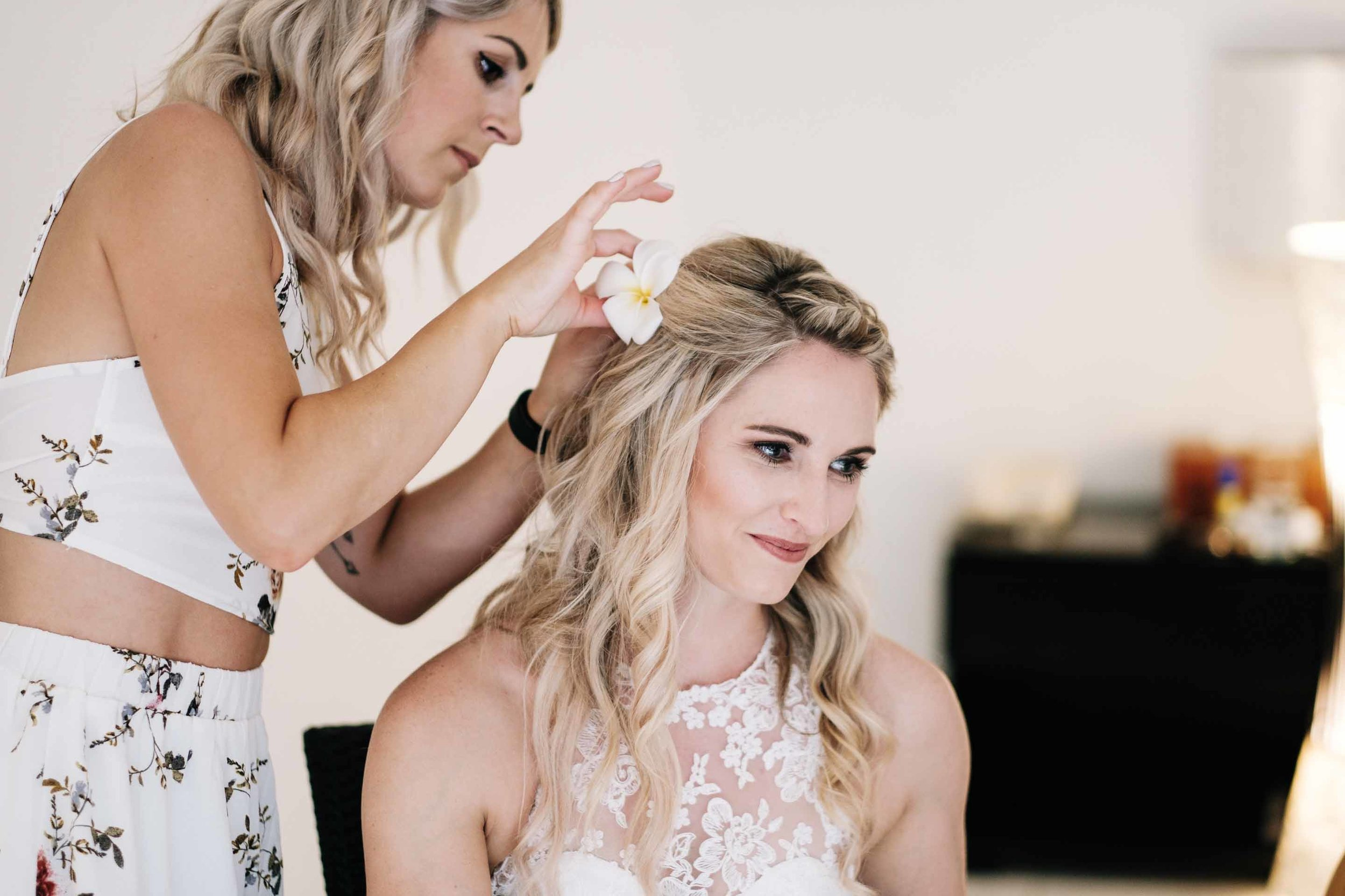 the makeup artist placing a flower into the brides hair