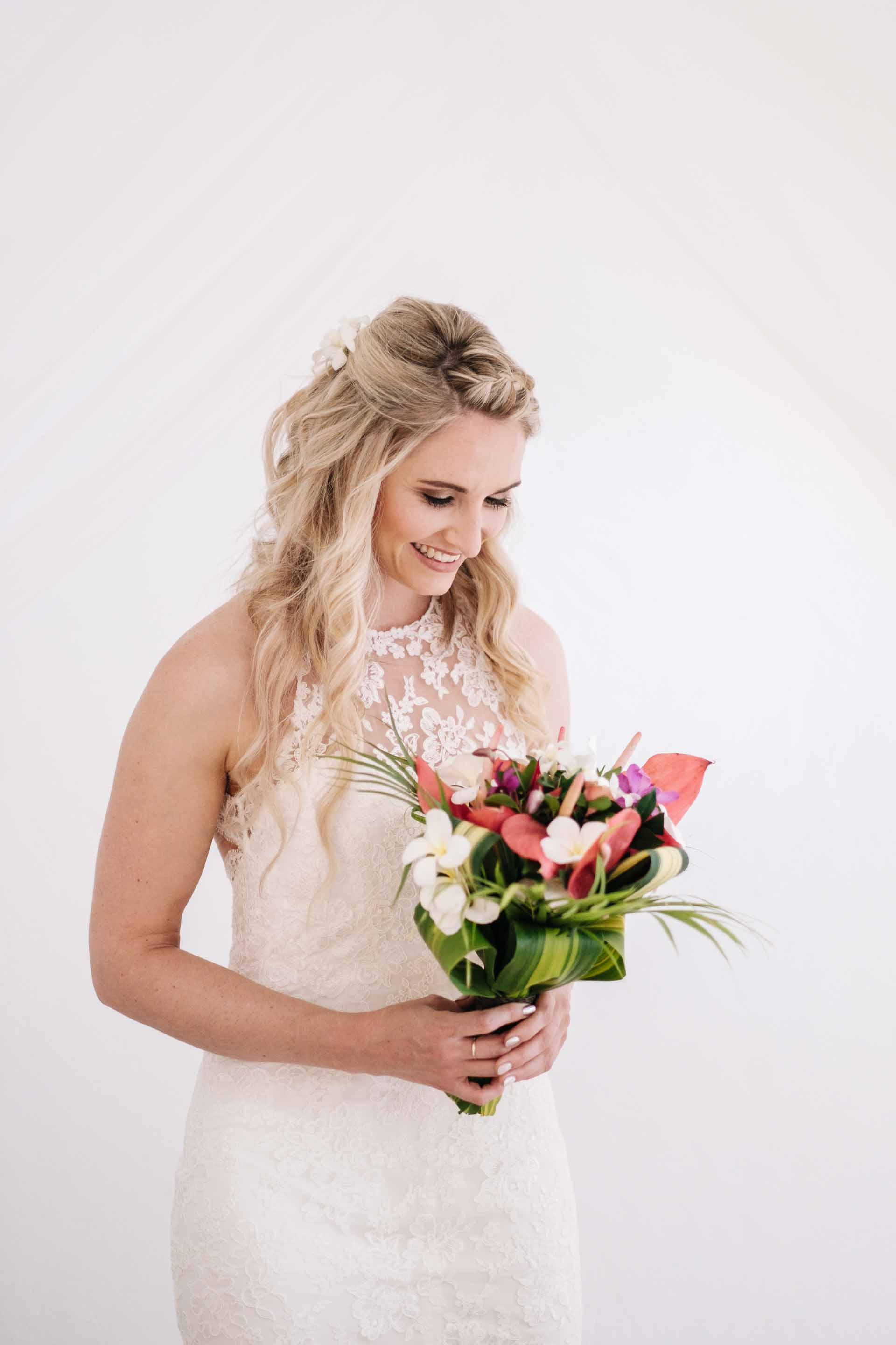 a portrait of the bride Holly with her bridal bouquet by her bed