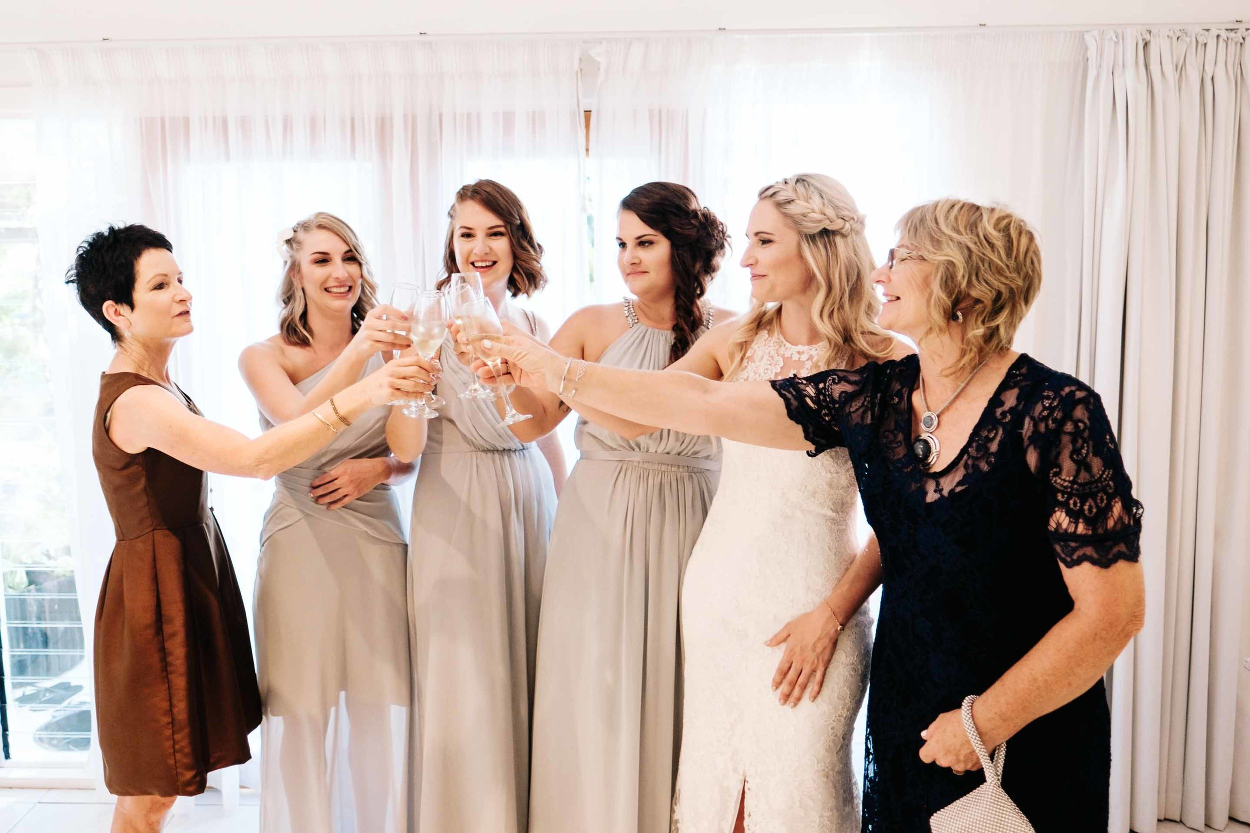 the bride and bridesmaids with the brides mother and aunt having a celebratory glass of champagne before the ceremony