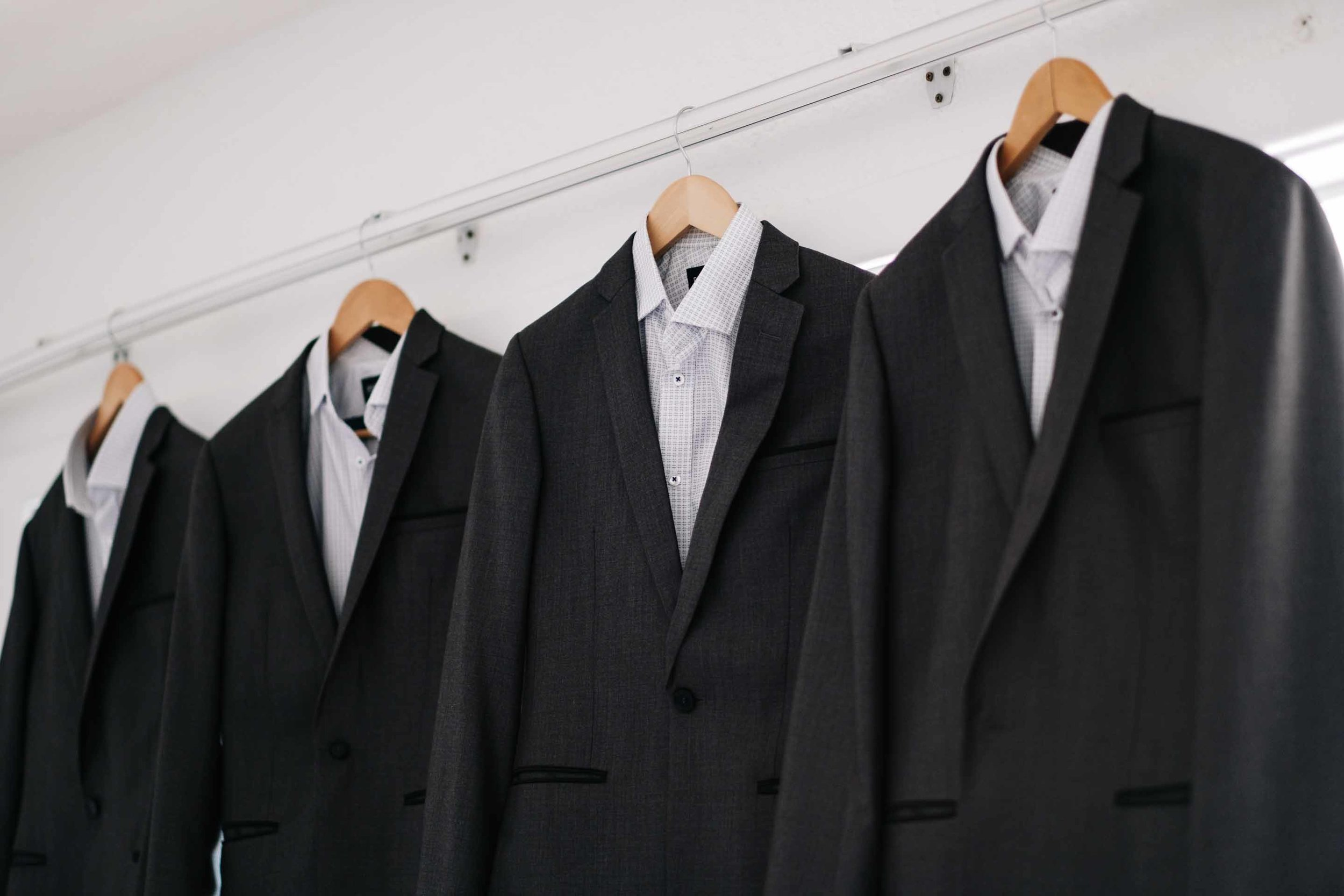 the groom and groomsmen suits hanging from customised wooden hangers