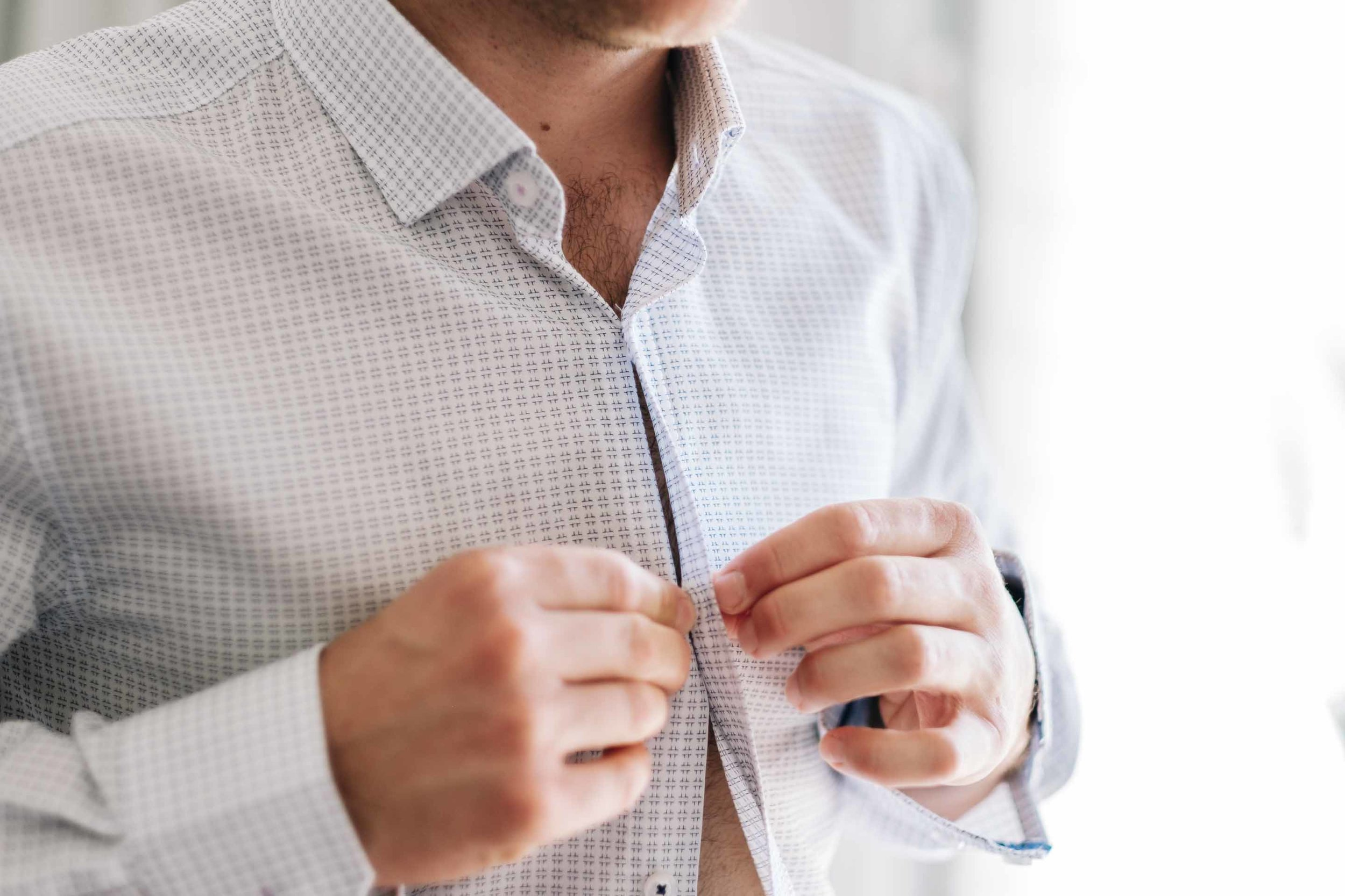 a closeup of the groom buttoning up his shirt