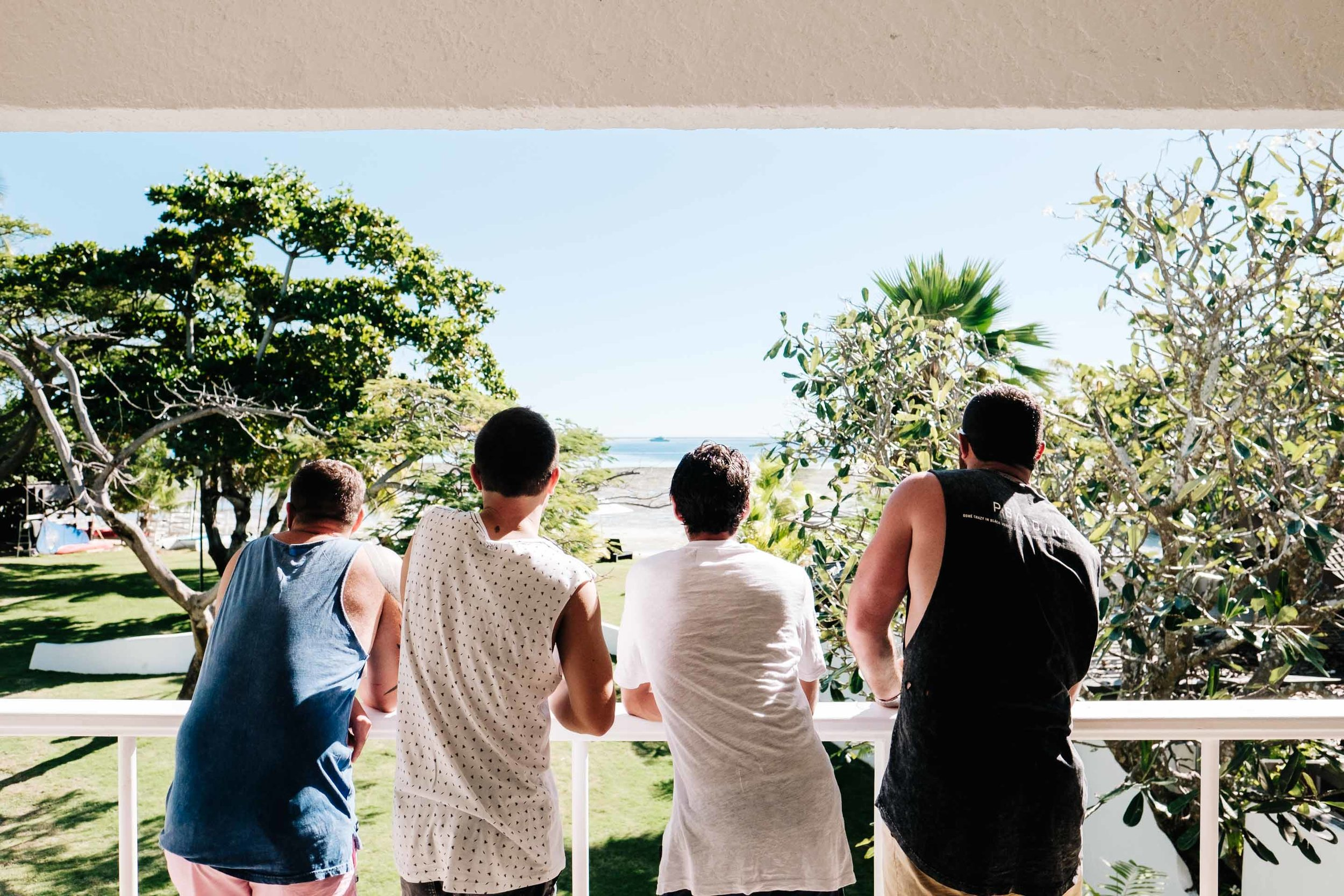 the groom and groomsmen sharing a beer while enjoying the view from their ocean view room