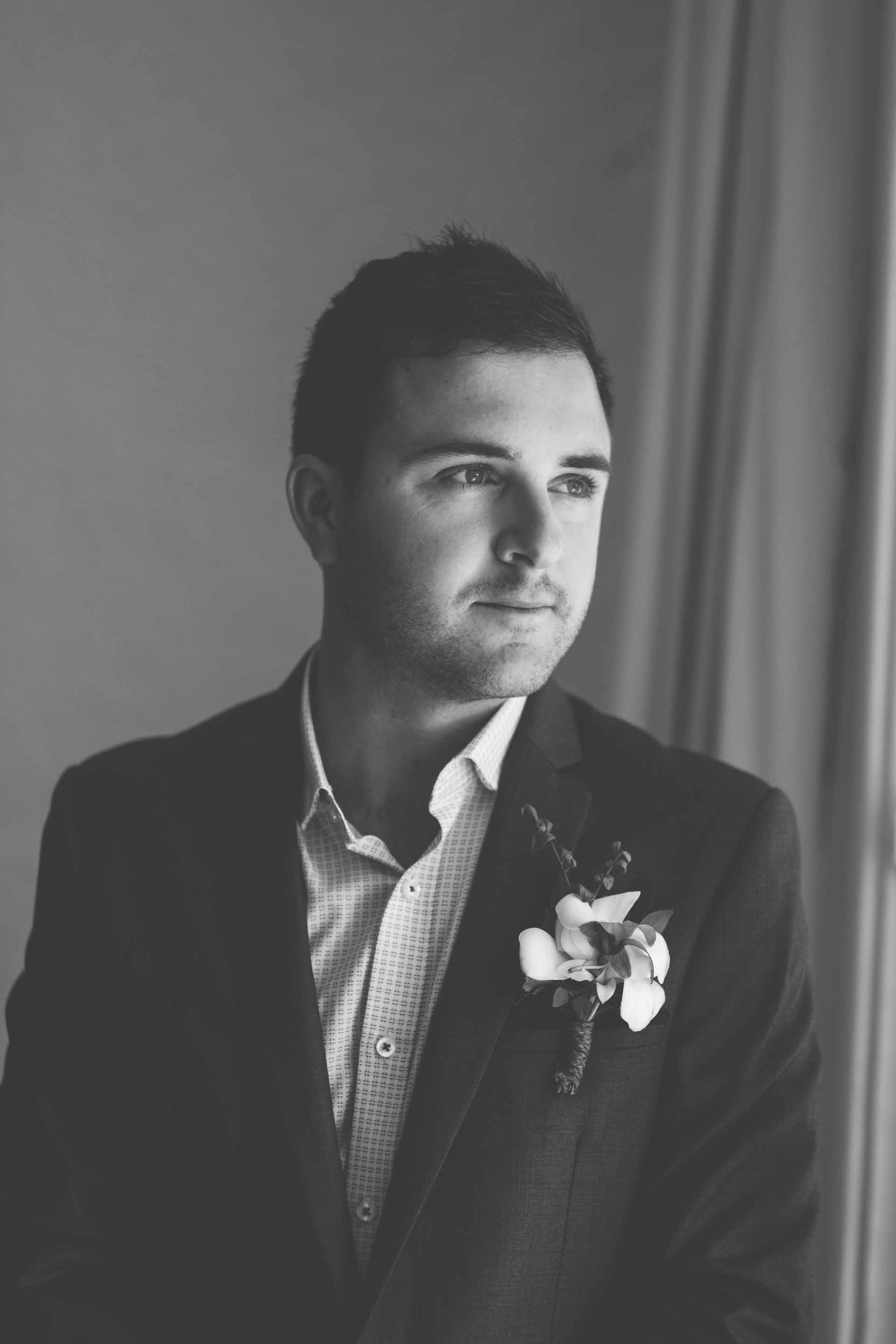a black and white portrait of the groom looking out the window wearing his wedding suite with boutonnière