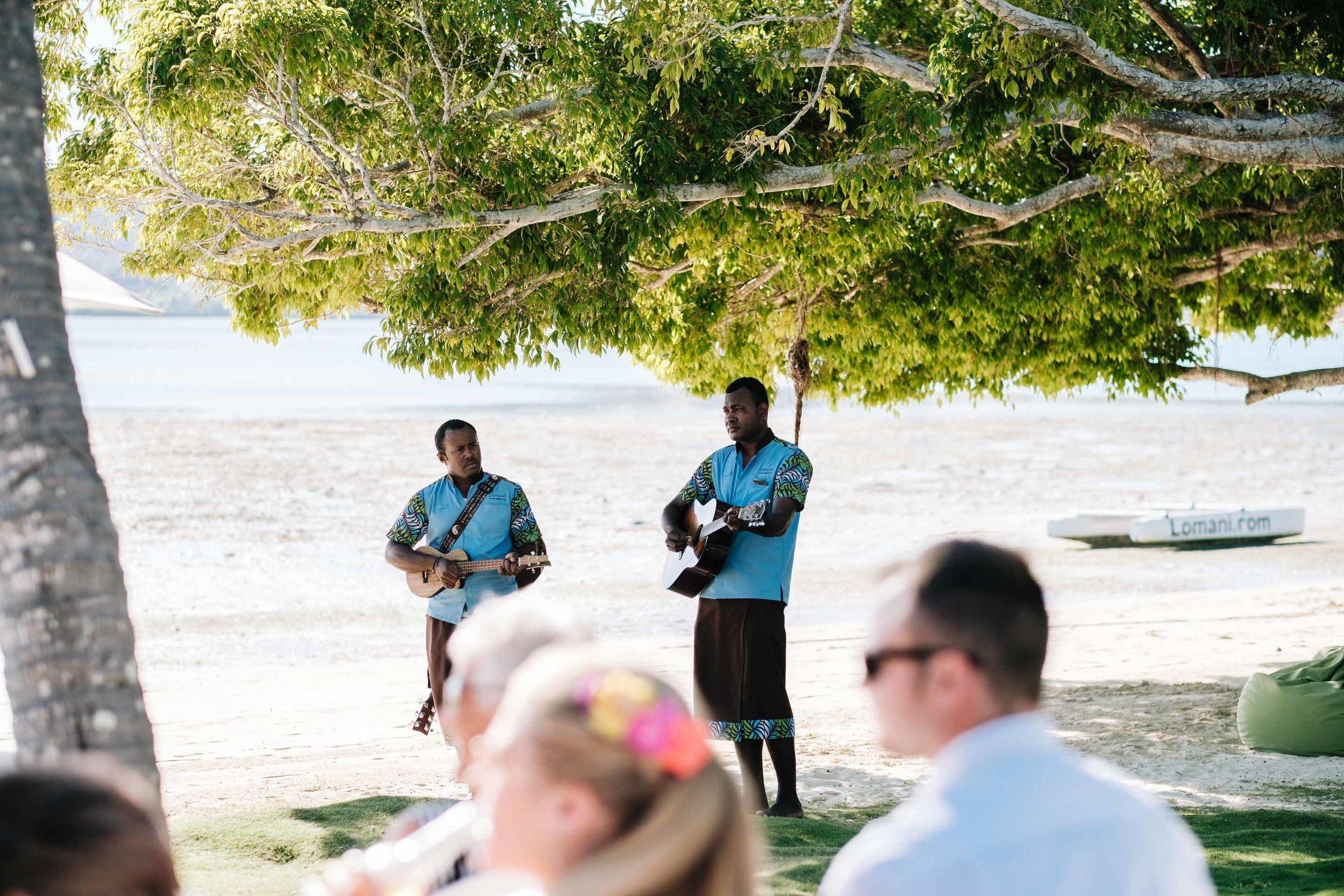 Serenaders under a tree strumming entertaining guests