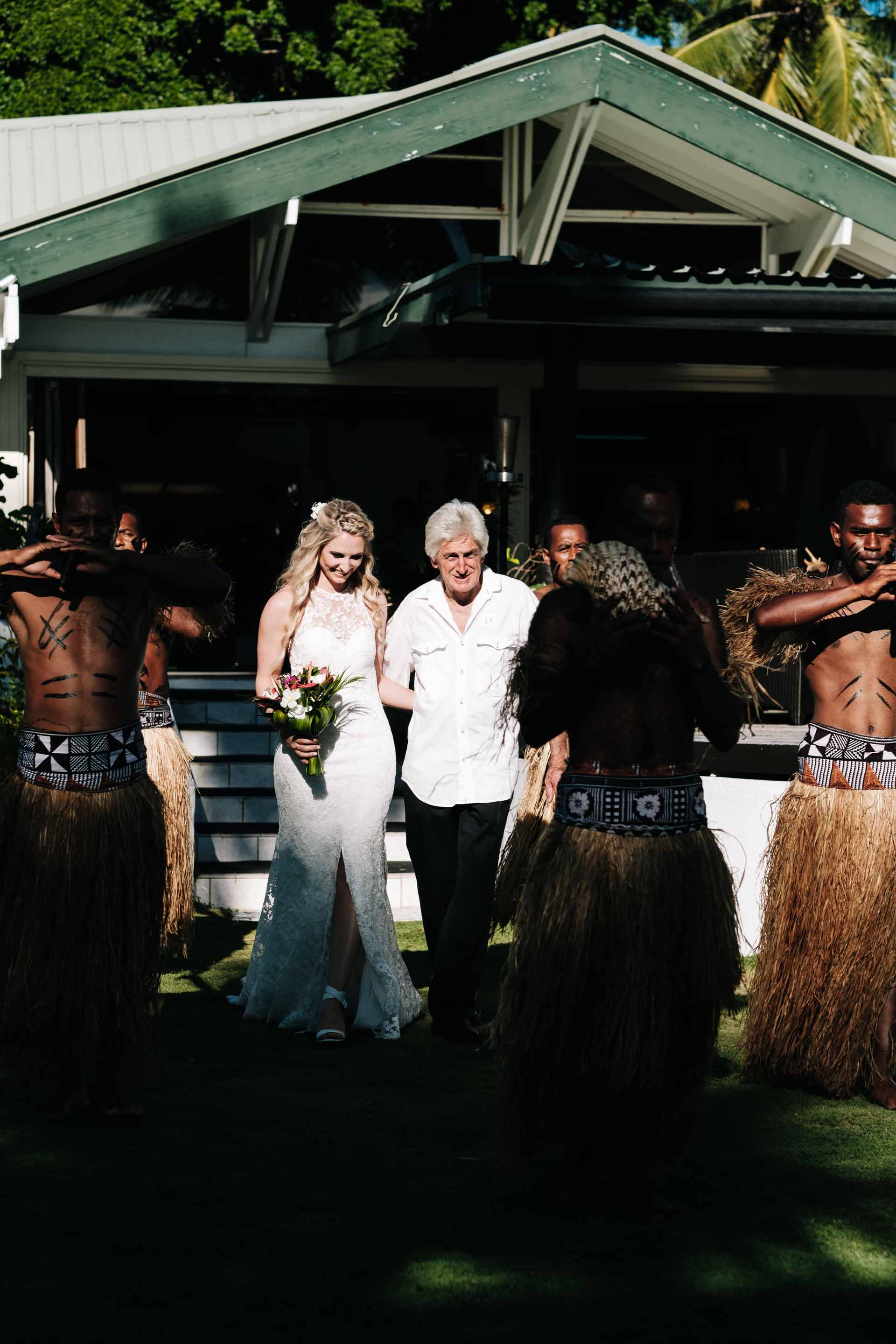 the bride and her father walking down the aisle escorted by Fijian warriors to the wedding arch