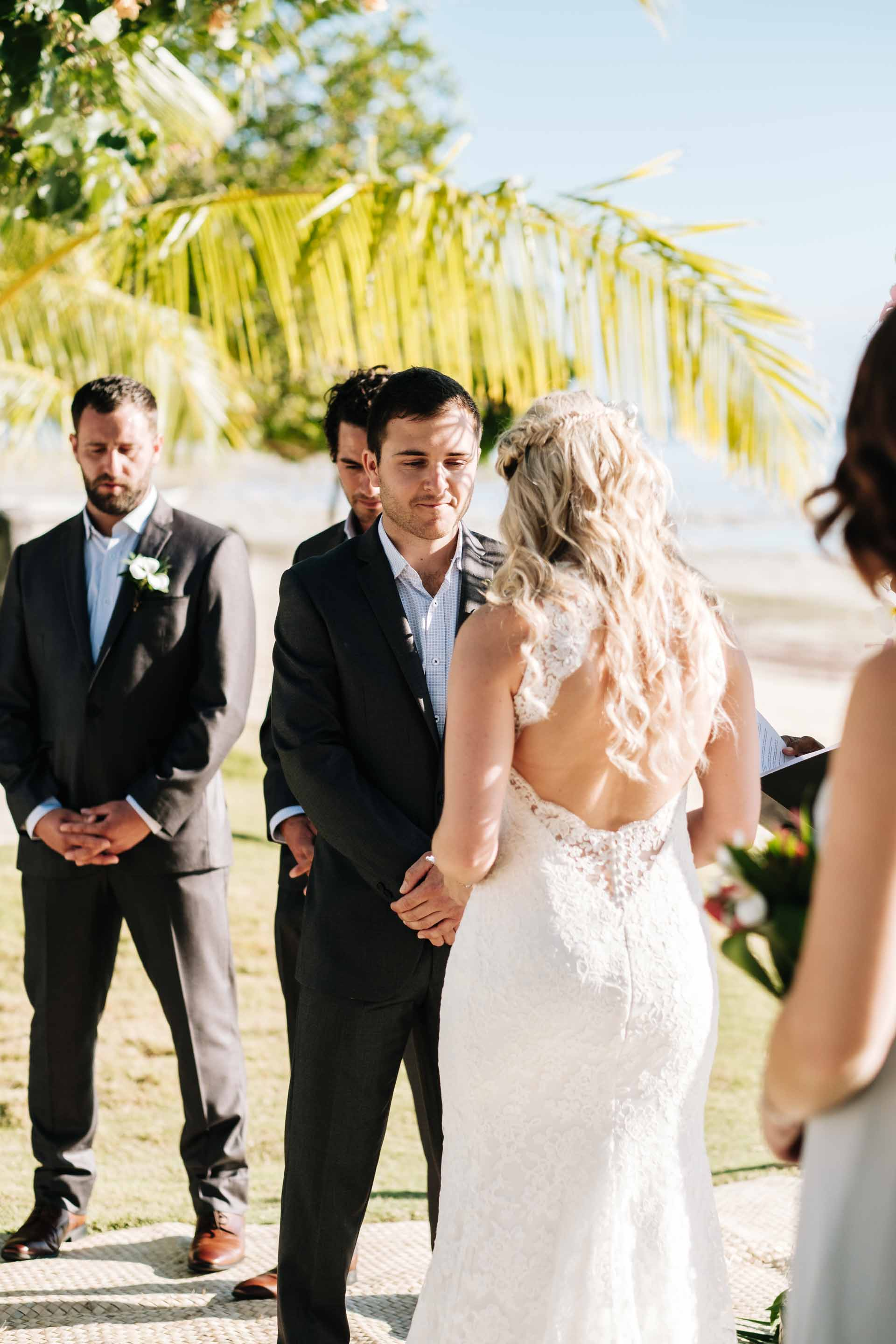 Cameron the groom listening to Holly the bride read her vows