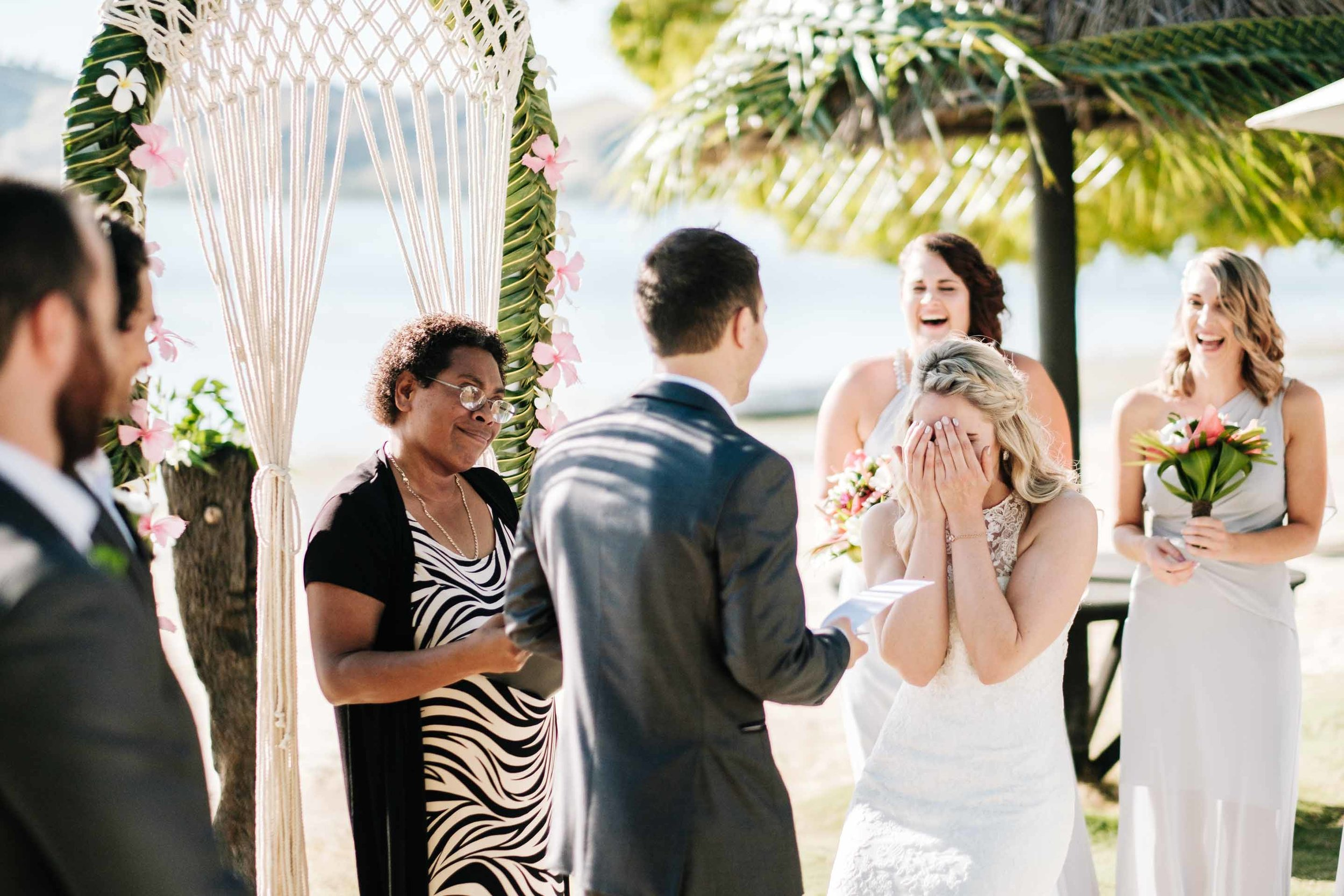 the bride reacting to the grooms vows by covering her face as she laughs