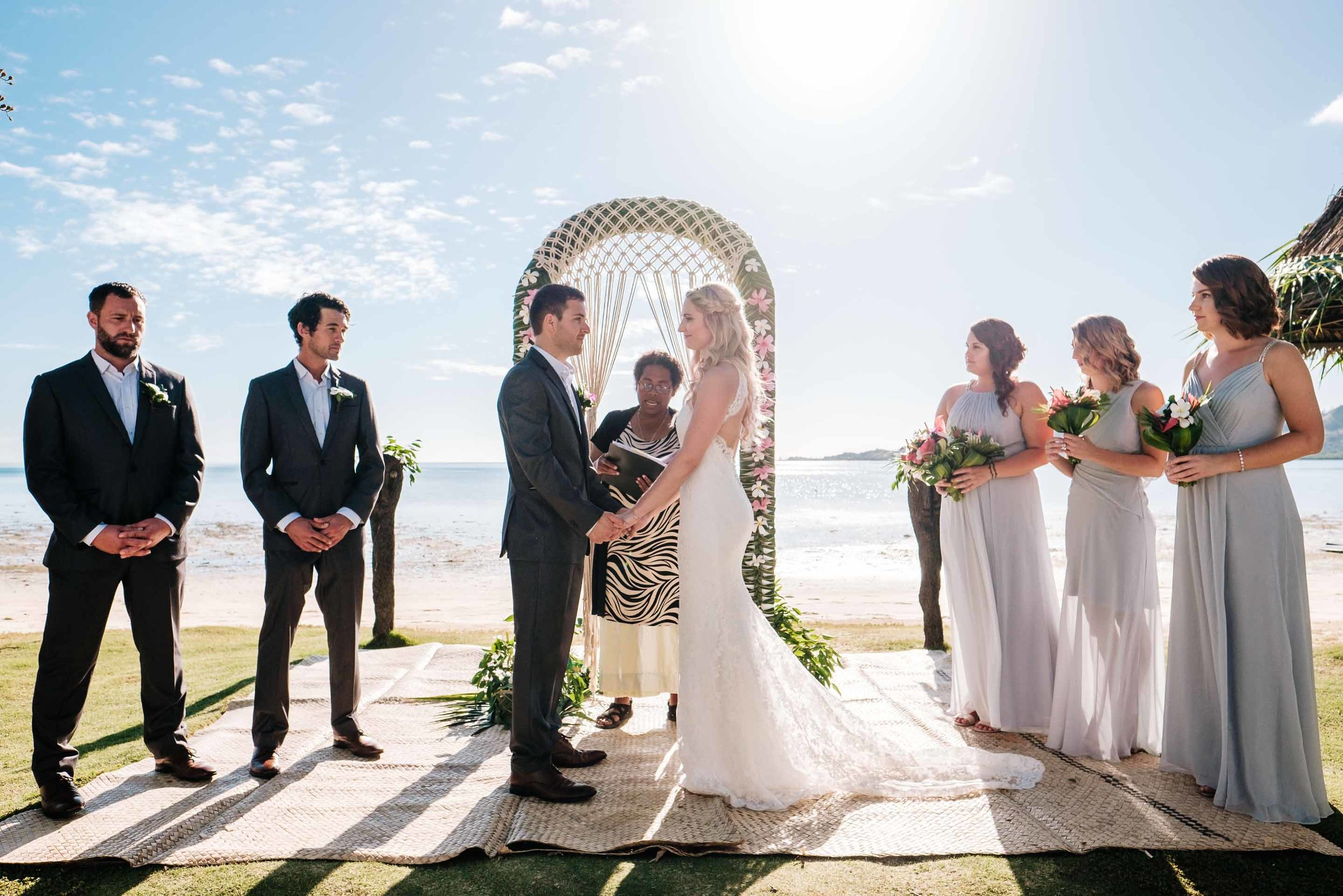 the bridal party at the wedding arch as the celebrant is about to conclude the ceremony