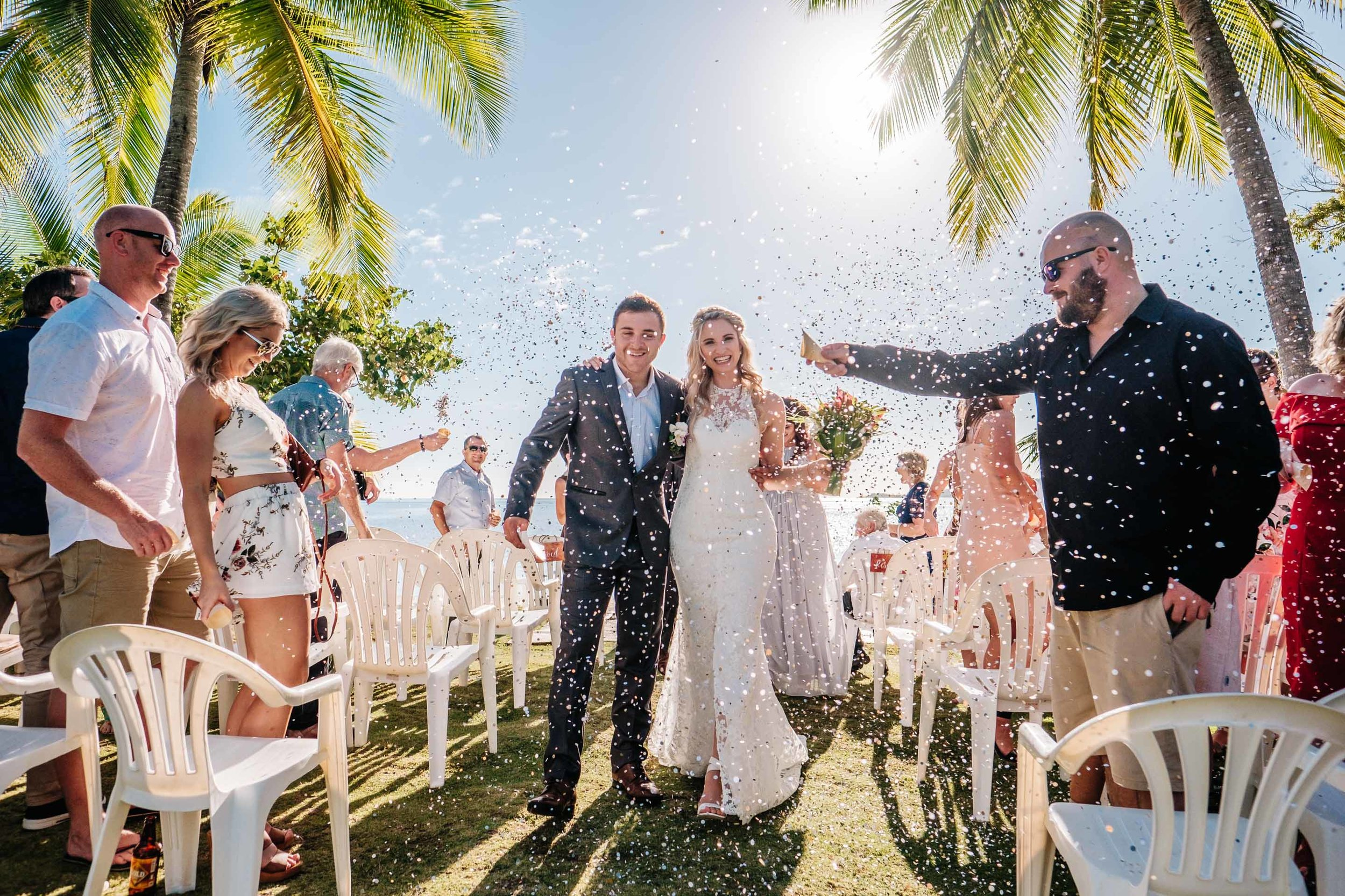 the newlyweds are showered in confetti as they walk down the aisle arm in arm