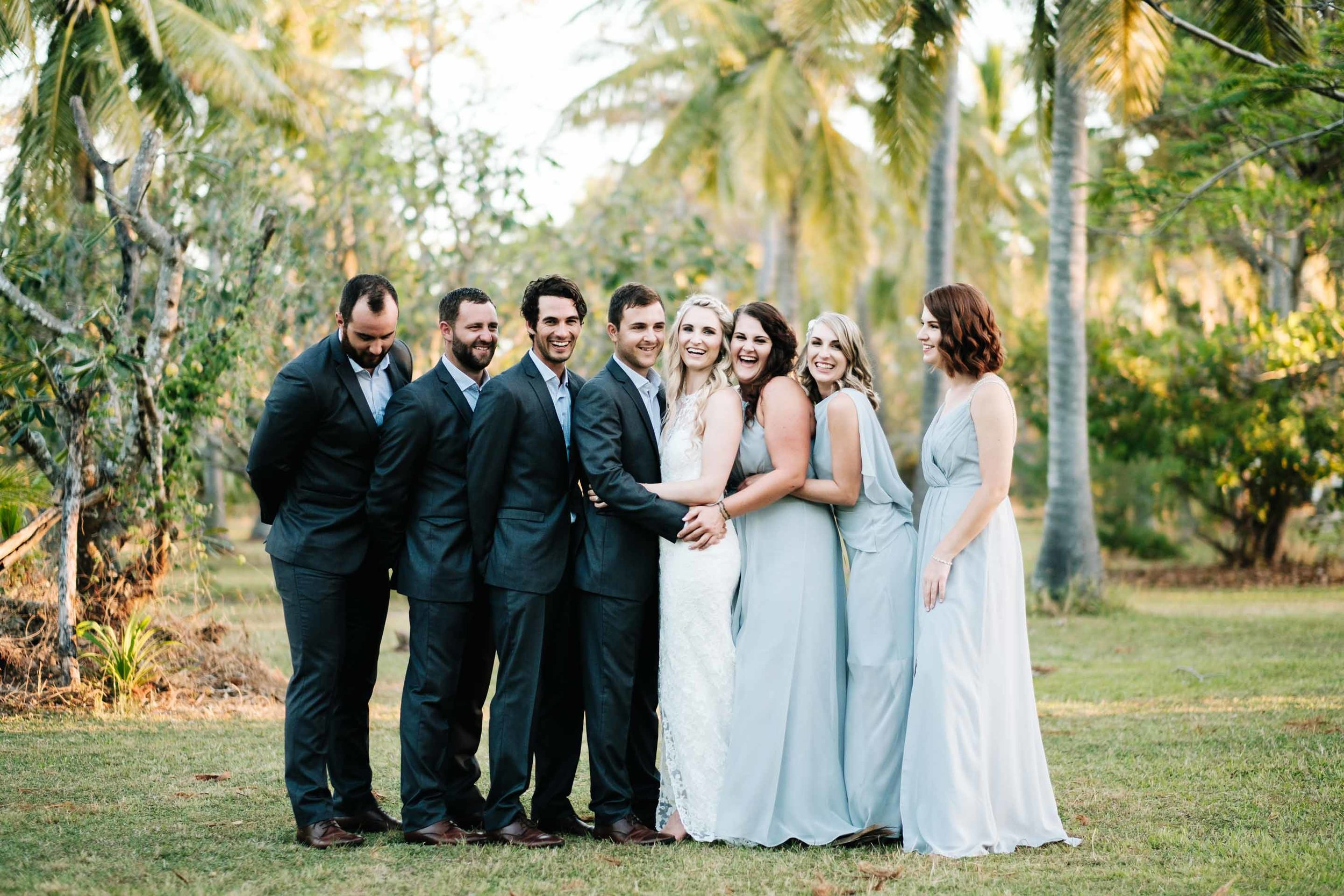 the bridal party together in the grounds behind Lomani Island Resort sharing a group hug