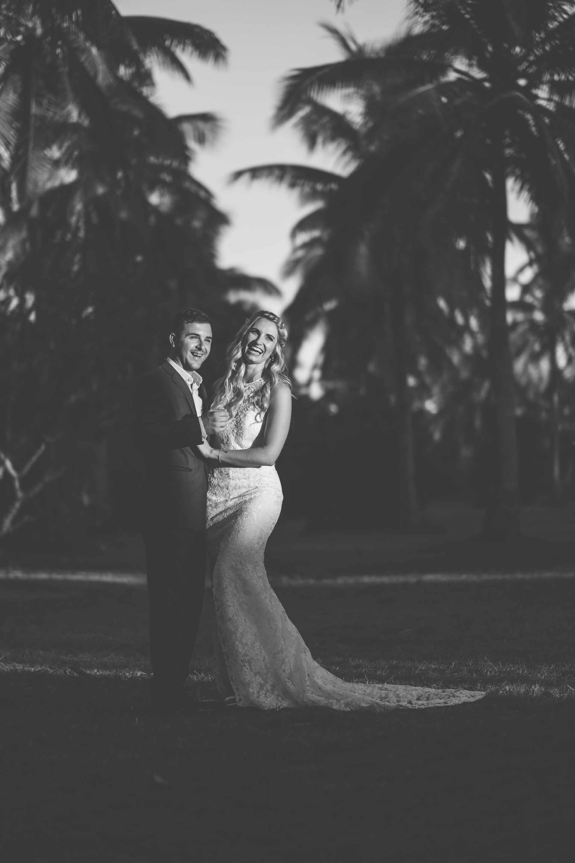 full length portrait of the bride and groom between rows of coconut trees in black and white
