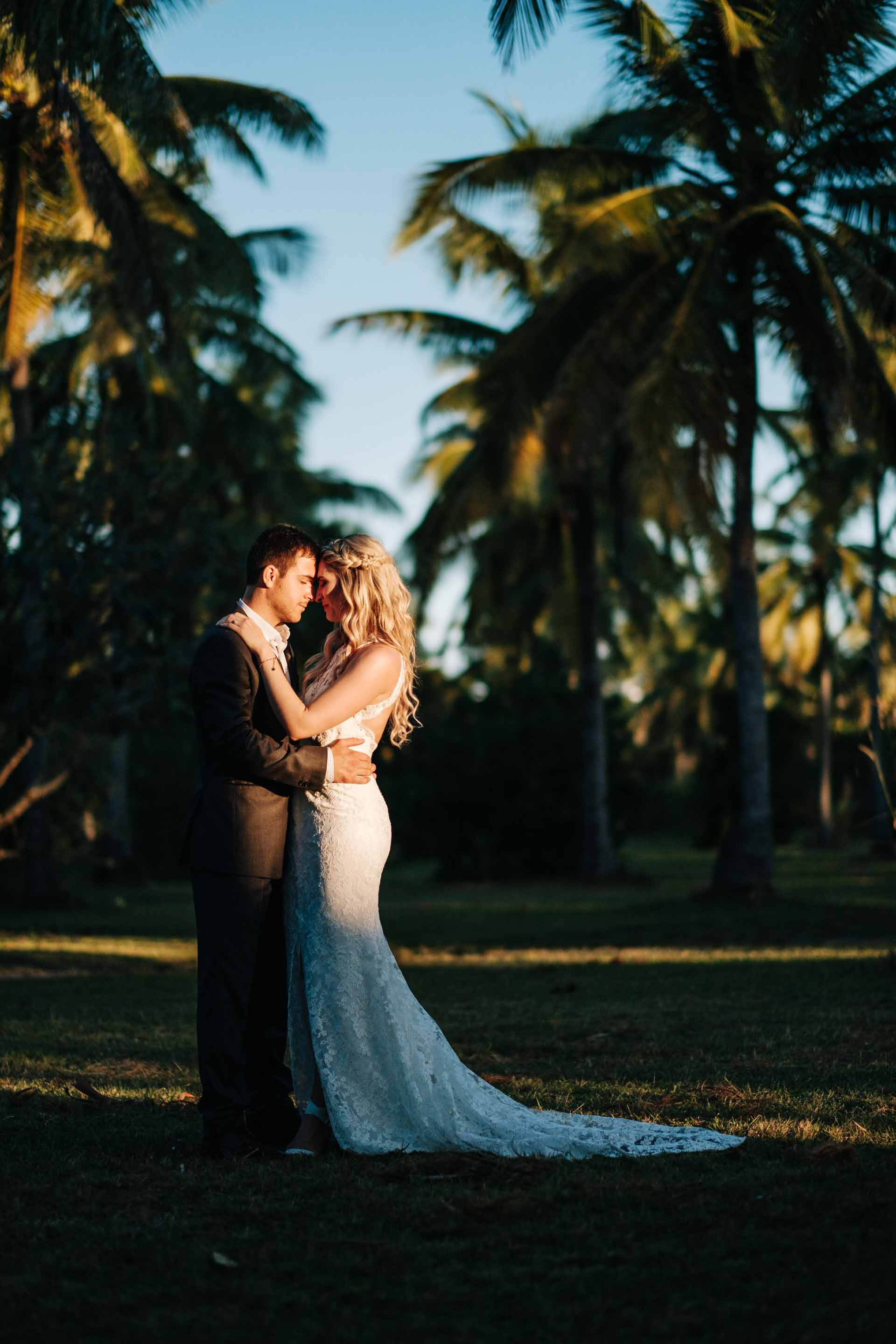 full length portrait of the bride and groom resting their bodies together between rows of coconut trees