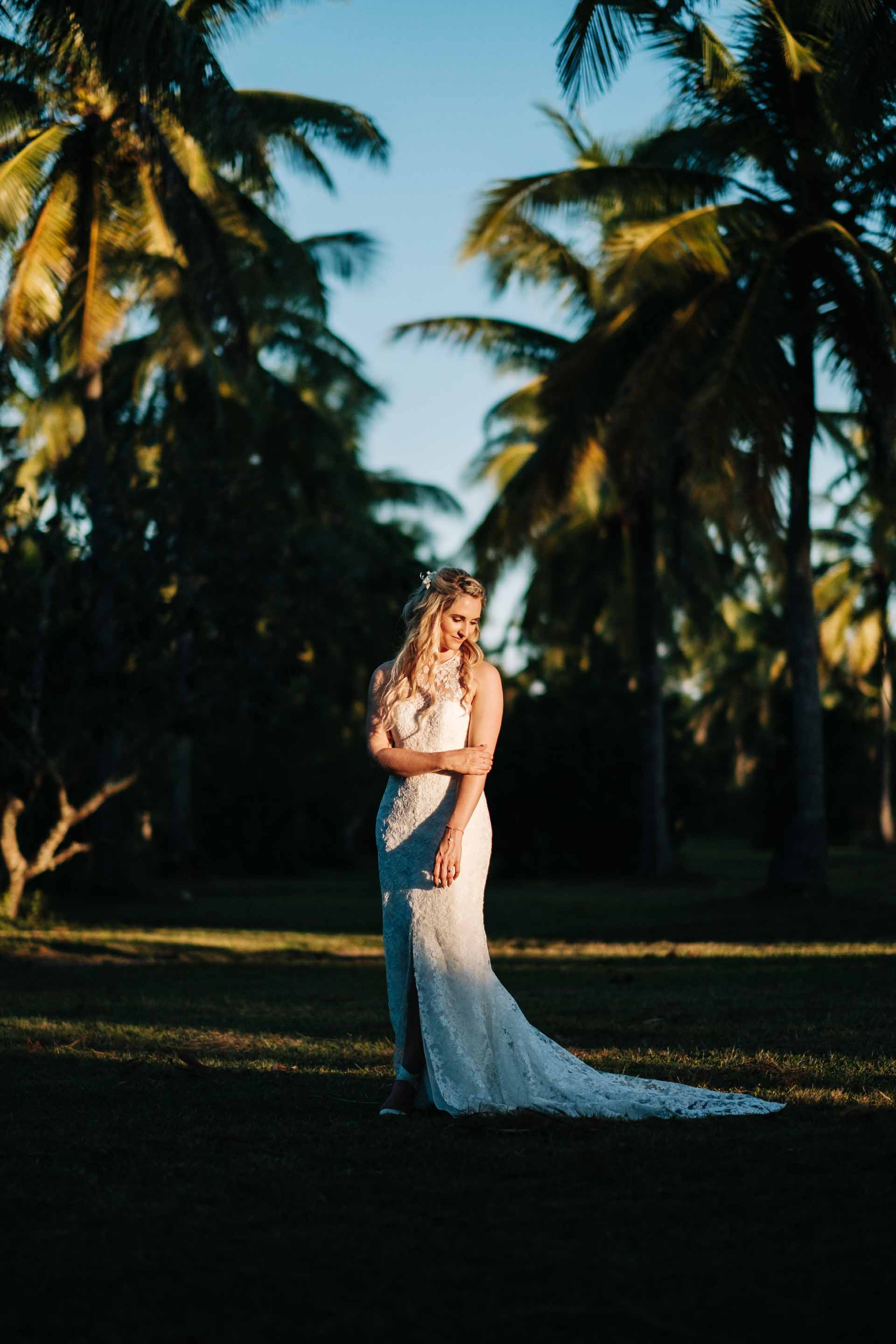 full length portrait of the bride between rows of coconut trees