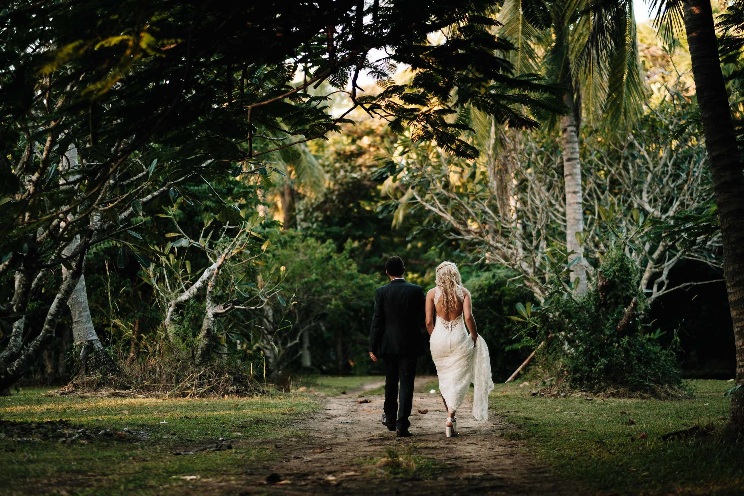 the bride and groom walking away together hand in hand under trees on a sandy dirt road