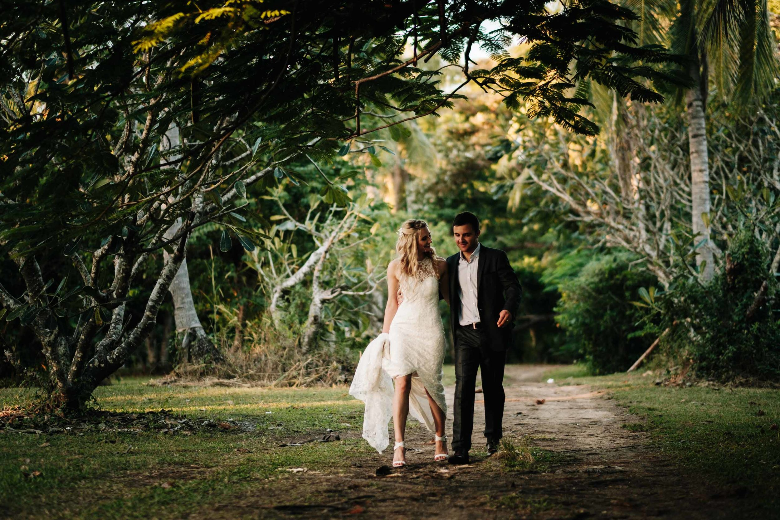 the bride and groom walking together hand in hand under trees on a sandy dirt road