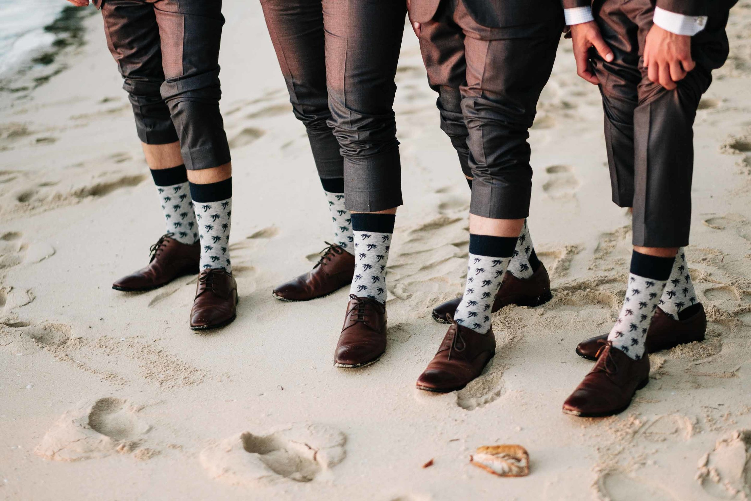 the groomsmen showing off their coconut tree socks on the white sand beach in front of the Resort