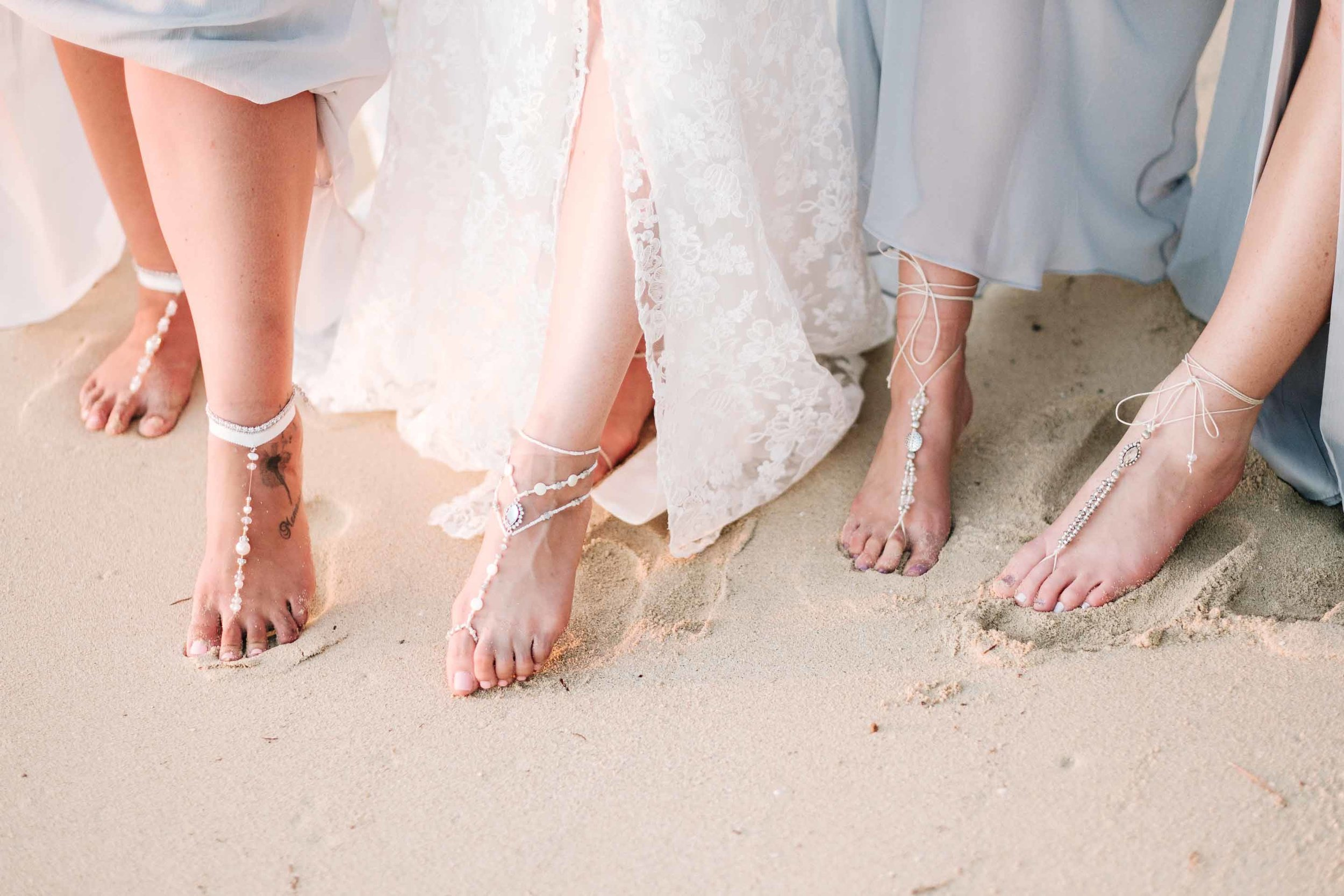 the bridesmaids showing off their foot jewellery on the white sand beach in front of the Resort