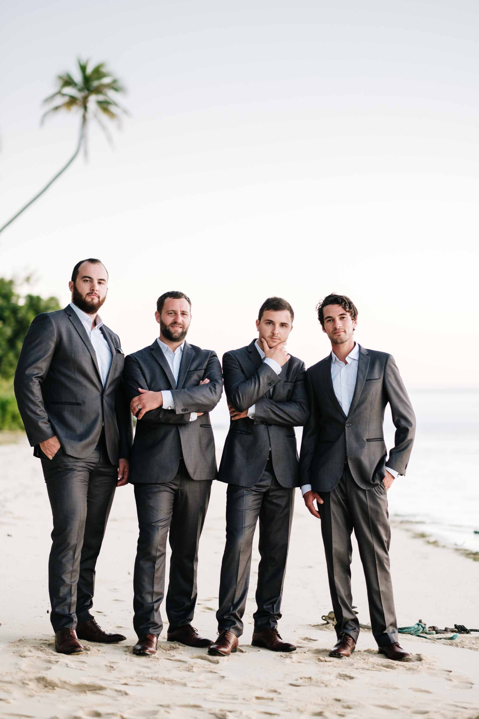 the groom and his groomsmen looking very suave on the beach at sunset