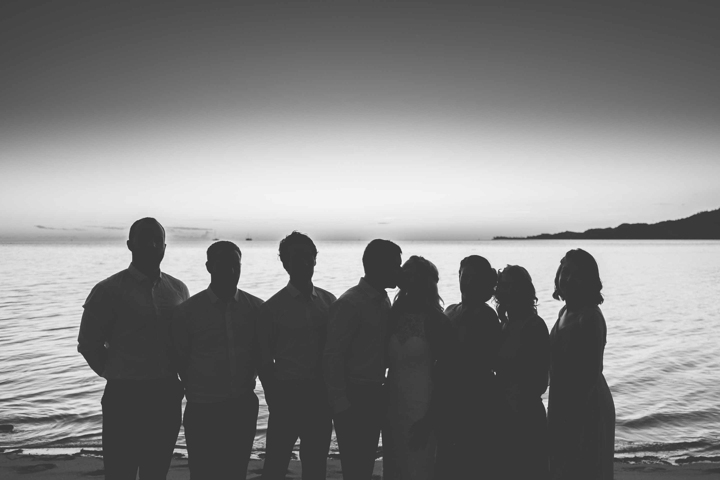 the bridal party silhouetted against the calm warm seas just after the sun has set in black and white