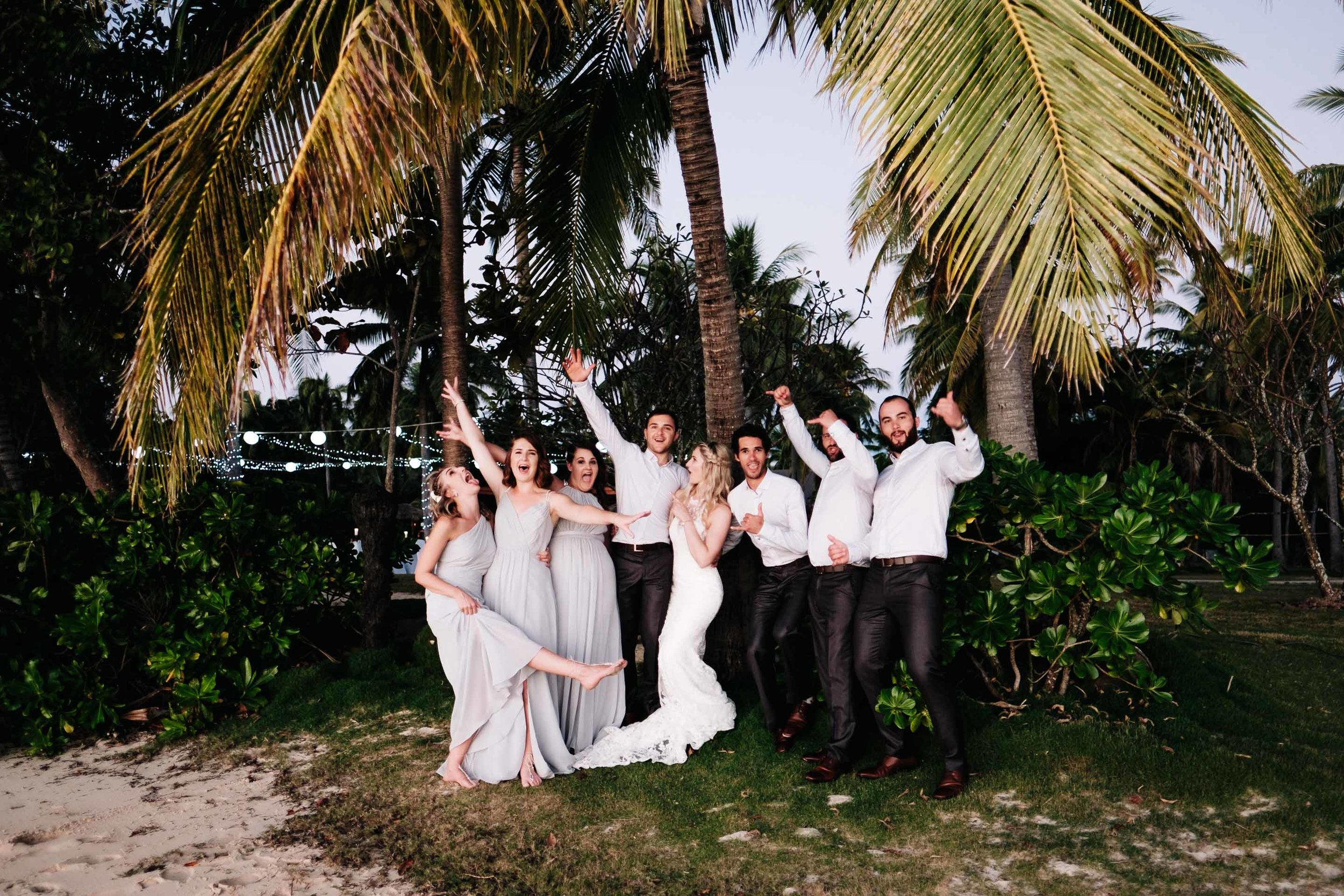 the bridal party having a light moment under a coconut tree next to the beach