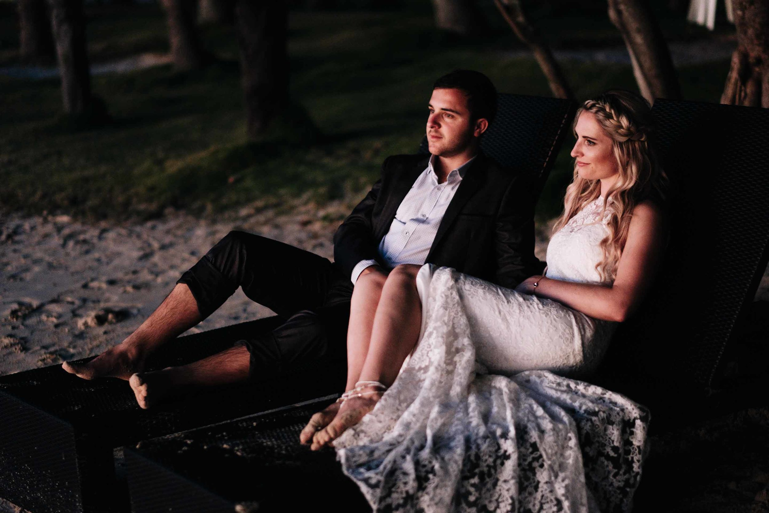 the bride and groom side by side on sun loungers as they wait for photos at sunset