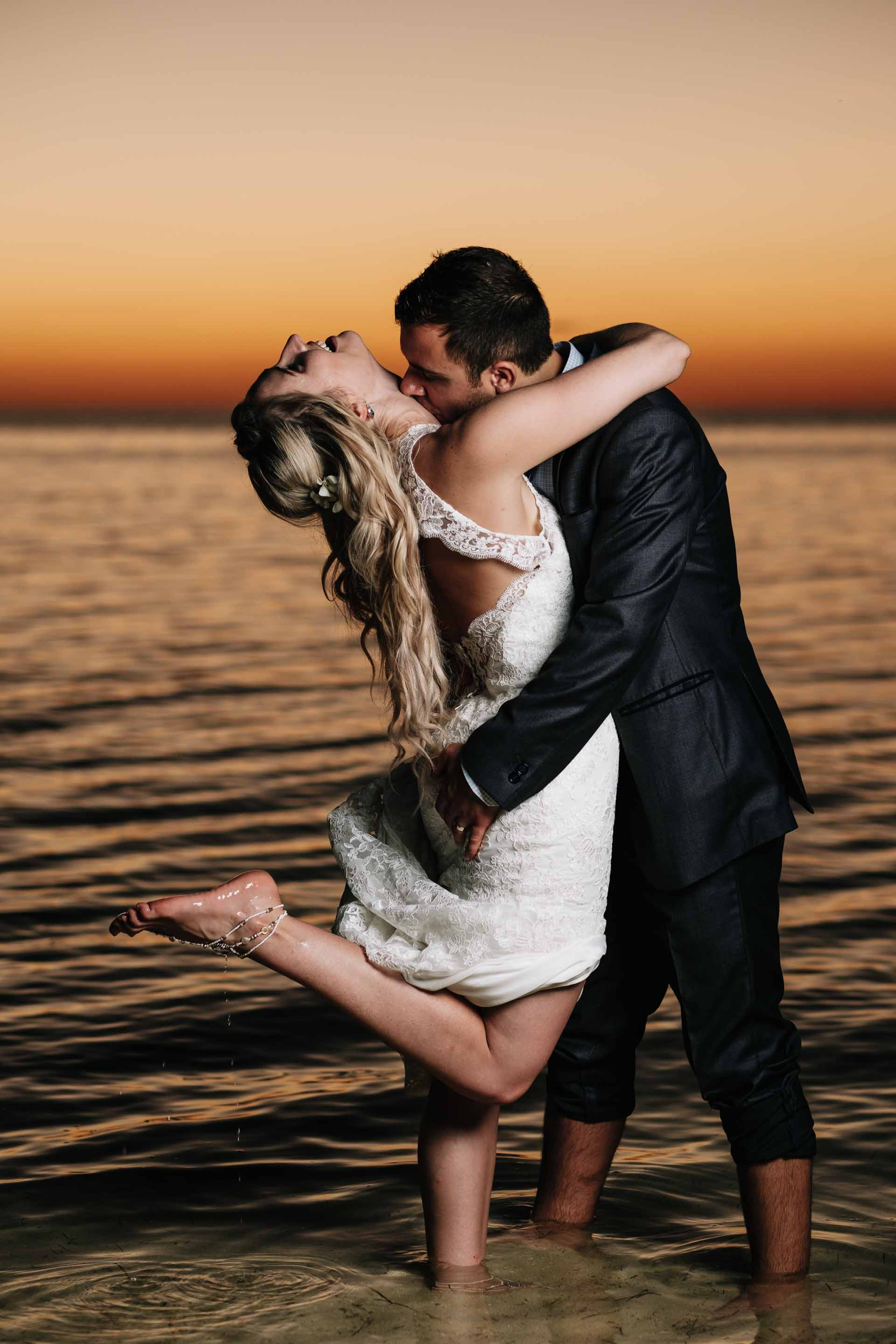 the bride and groom have fun in the warm water with the stunning backdrop of deep reds and oranges of a sunset