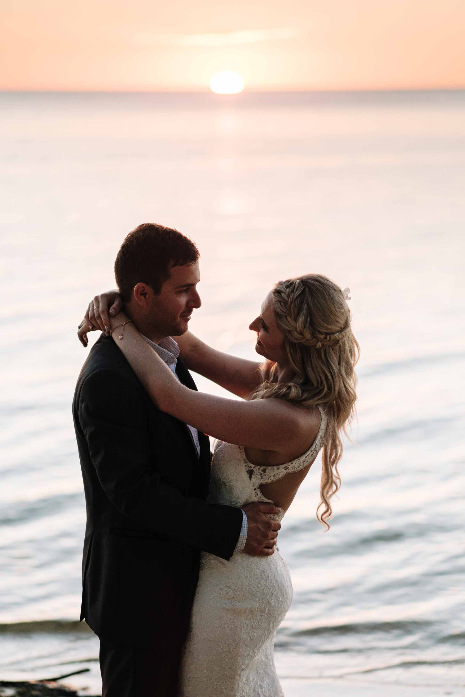 the bride and groom hold each other as the sun is about to dip behind the horizon