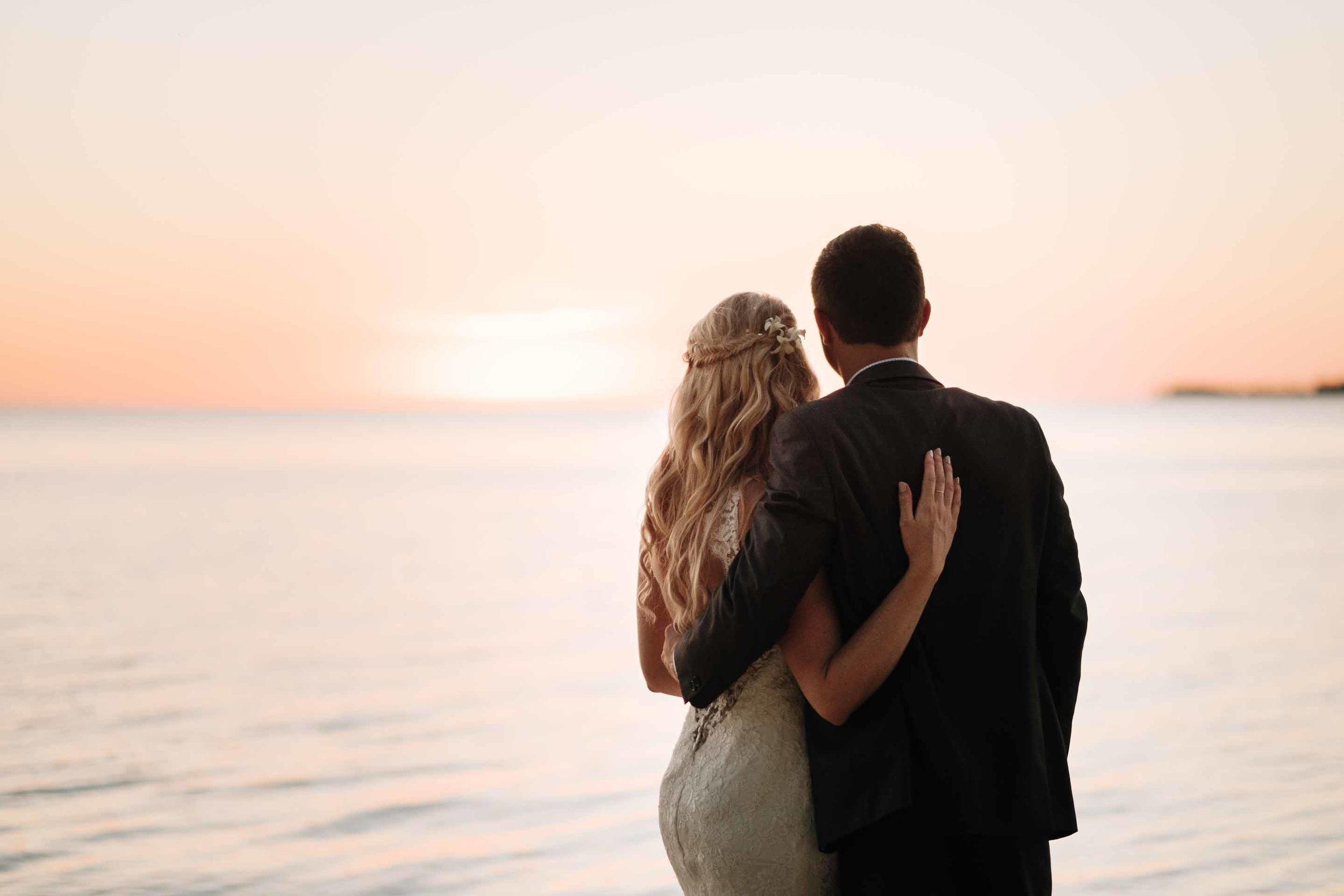 the bride and groom watch as their first sunset as husband and wife disappears behind the horizon