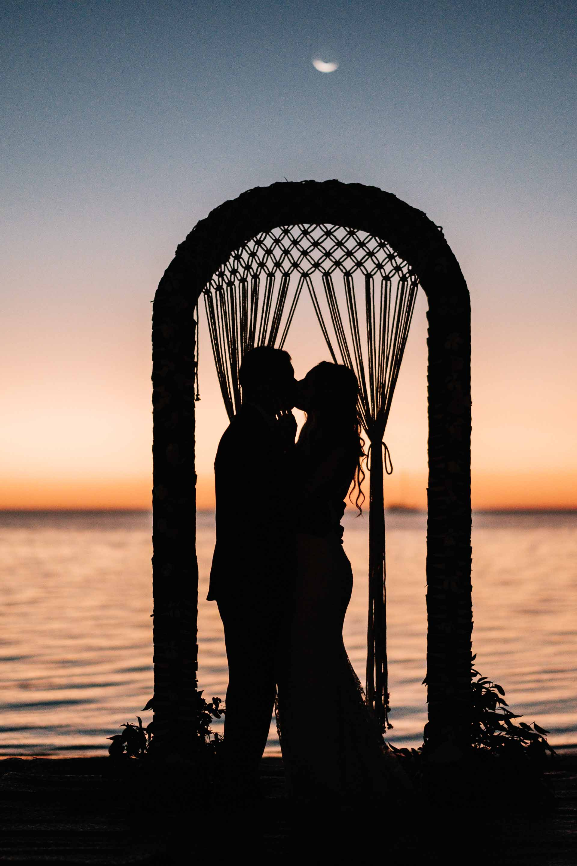 the bride & groom share a kiss silhouetted against the calm warm seas and their macrame wedding arch just after the sun has set with the moon above them