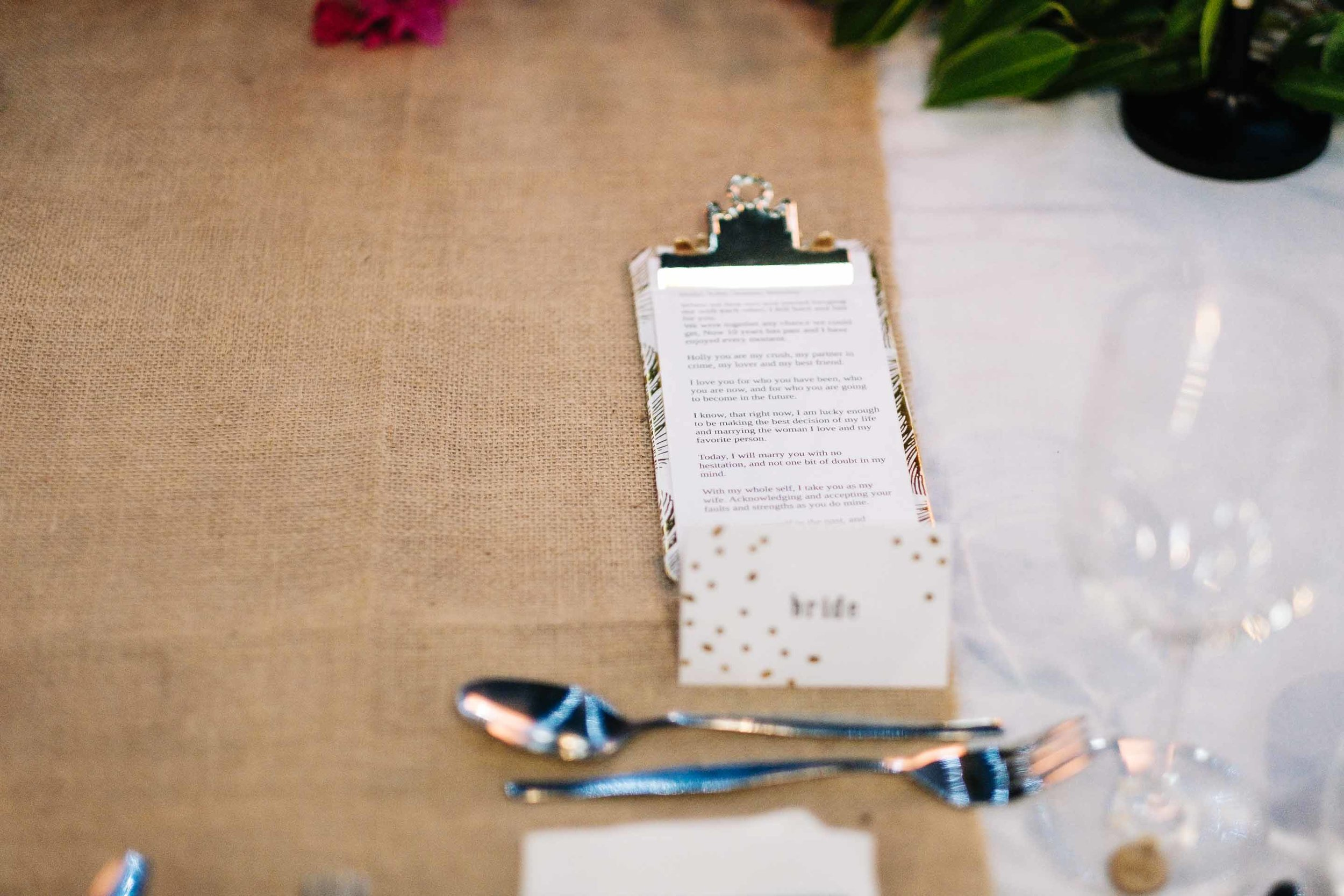 the grooms vows on his custom clipboard on the bridal table