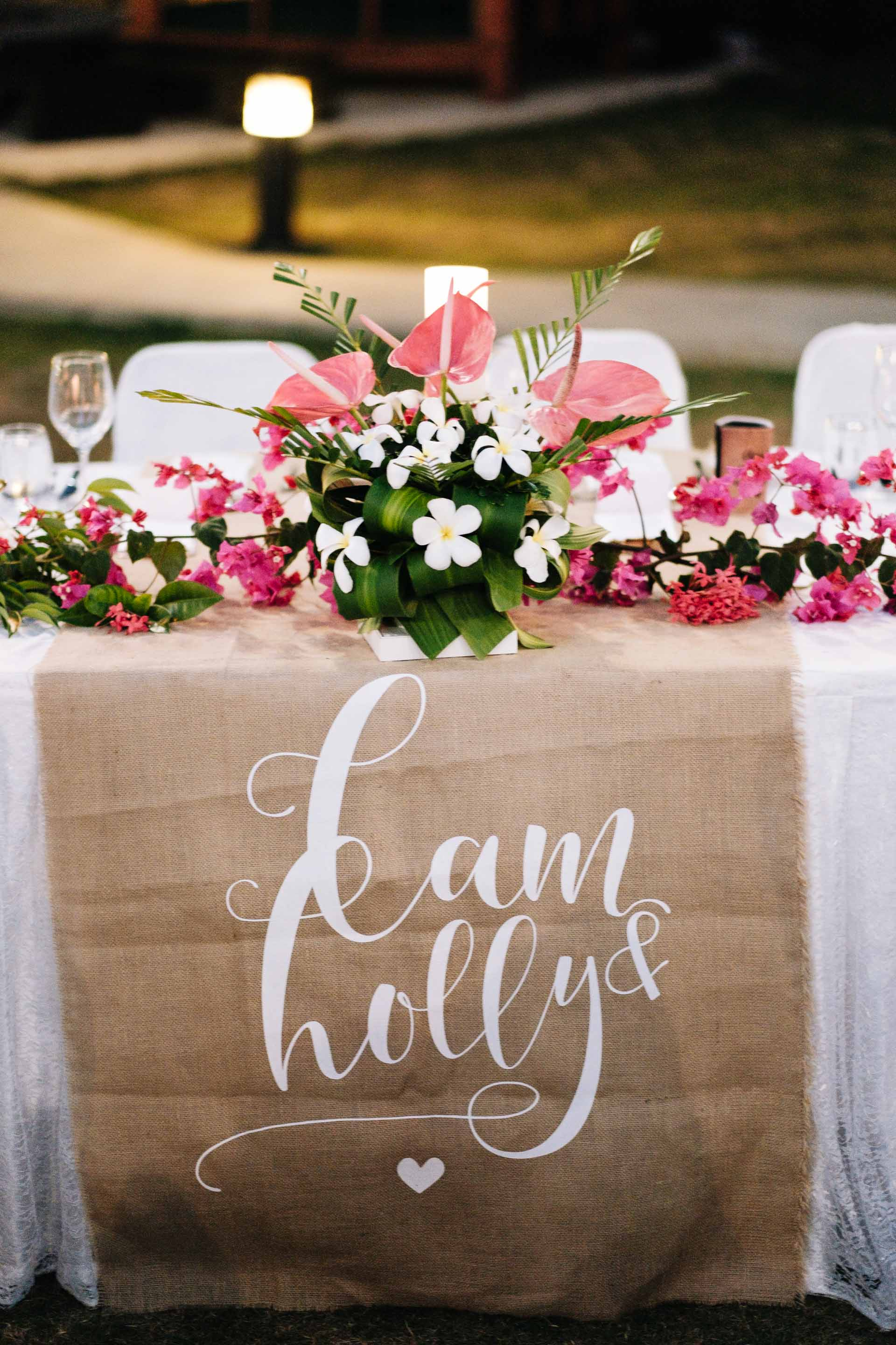 the head table with a burlap table runner printed with the bride and grooms names