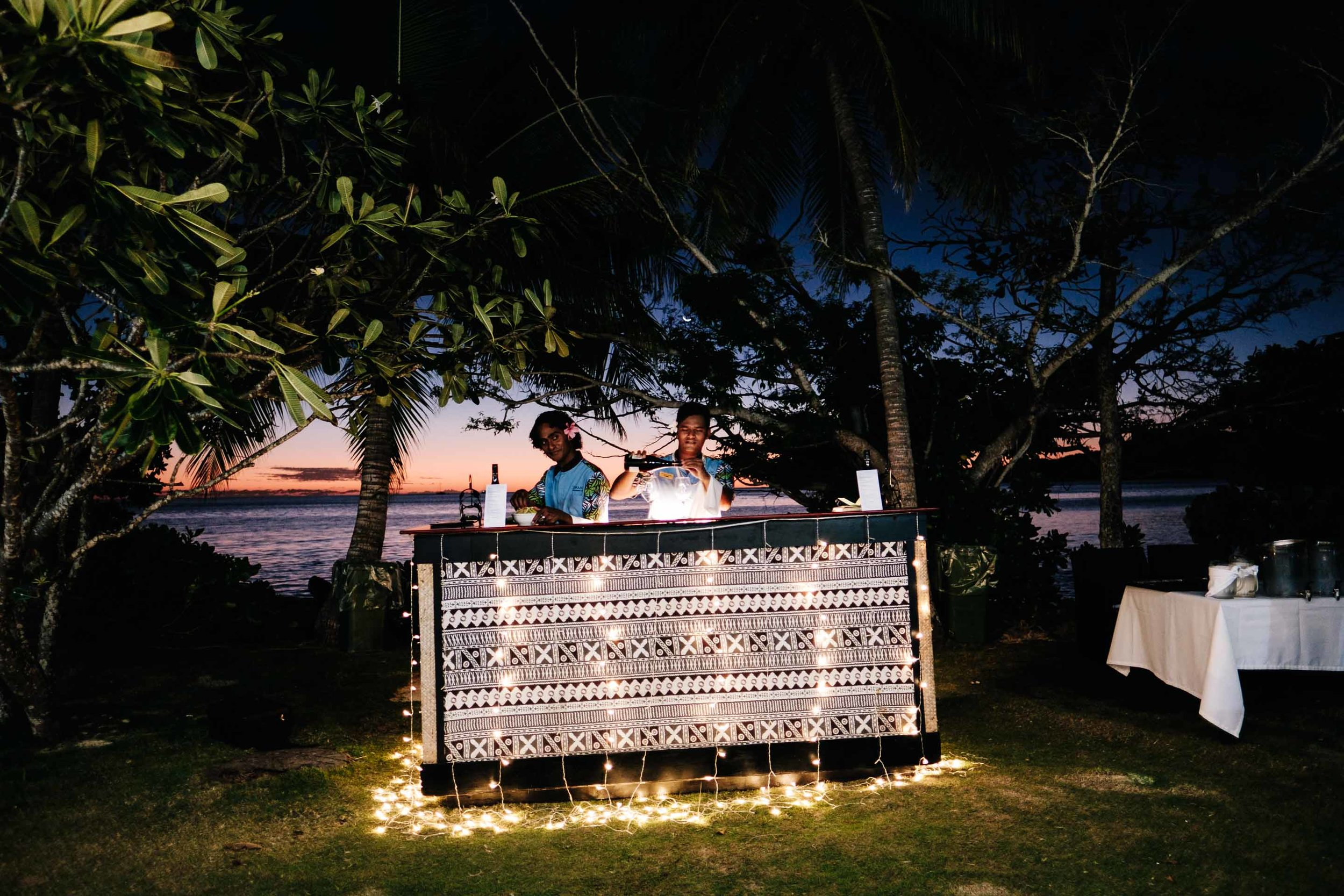 the bar staff mixing drinks behind the outdoor bar with traditional tapa print and surrounded by fairy lights