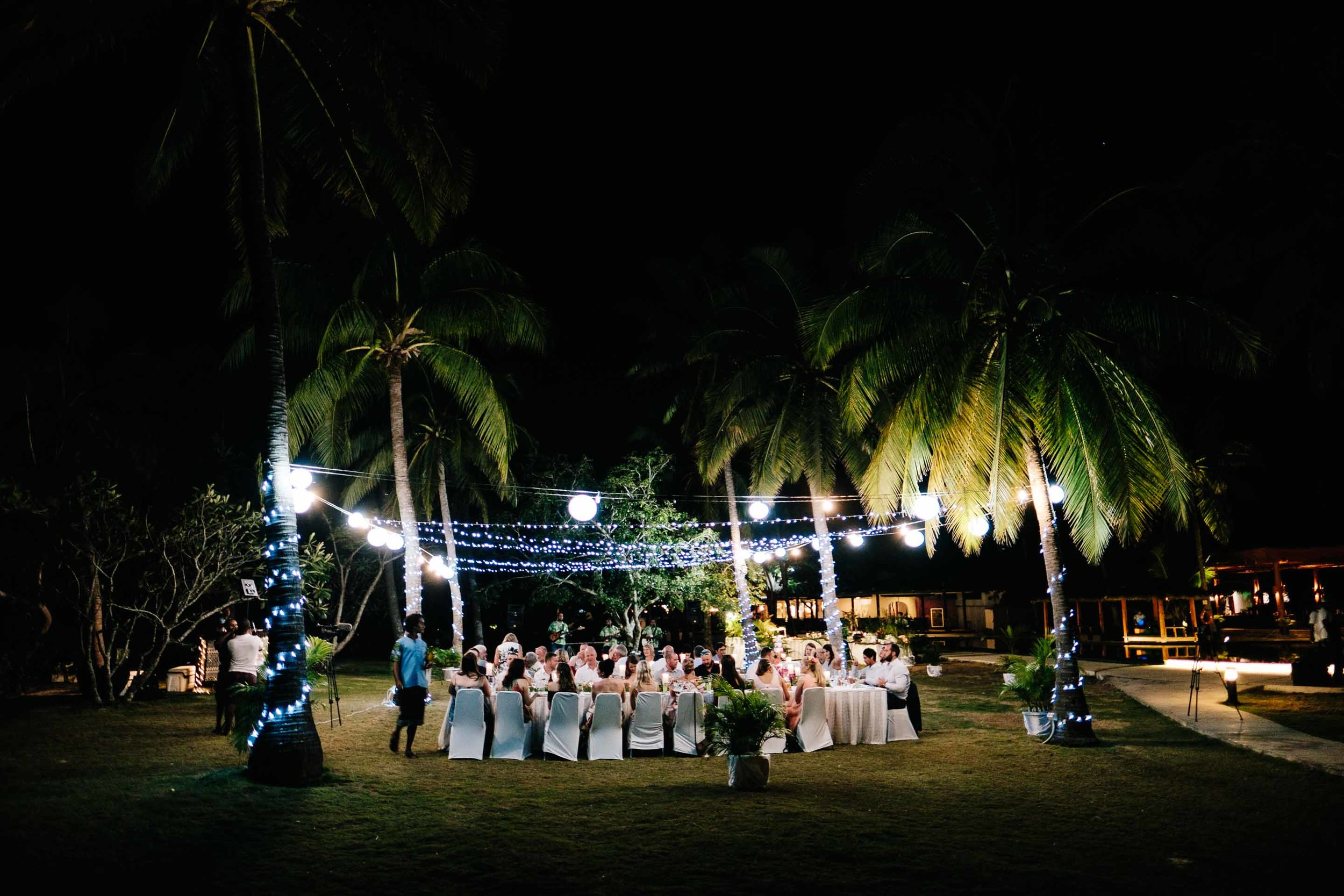 the wedding reception held under the trees by the beach at Lomani Island Resort