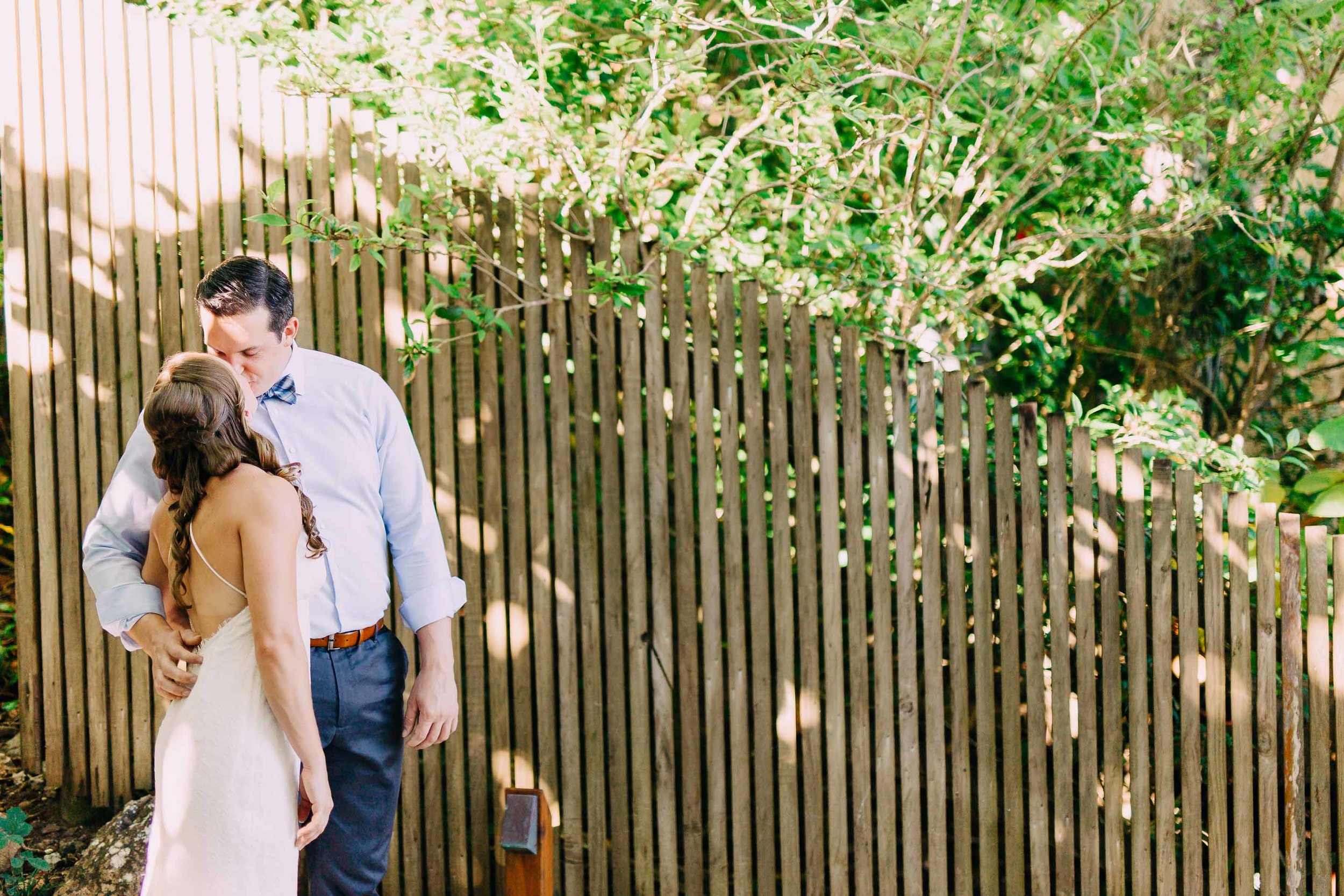 Fiji bride and groom kiss in front of a bamboo wall.