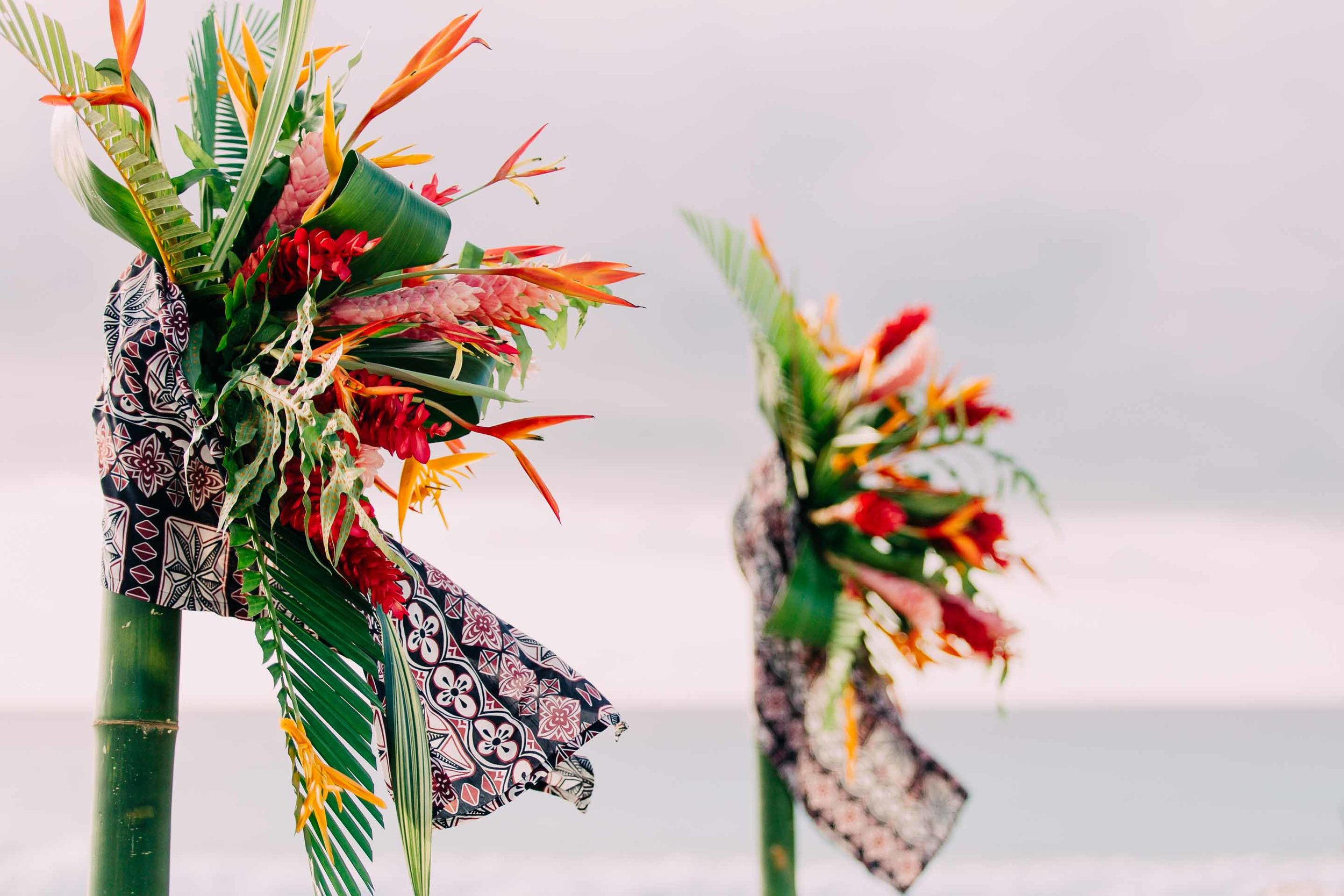 Wedding arch decorations Fijian tapa cloth, tropical Fiji flowers and leaves.