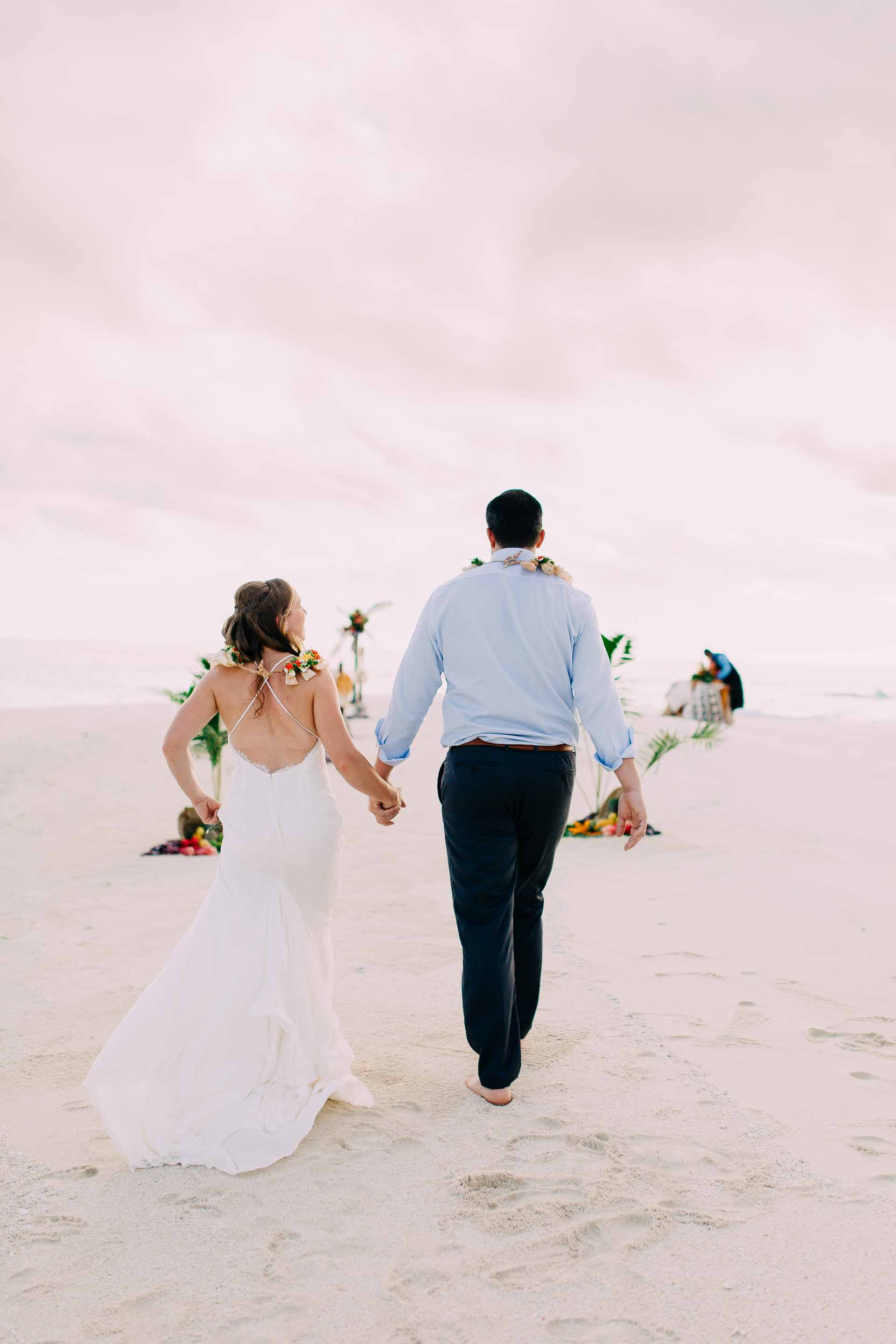 Bride and Groom walk up the aisle to exchange vows at their sand bar wedding.