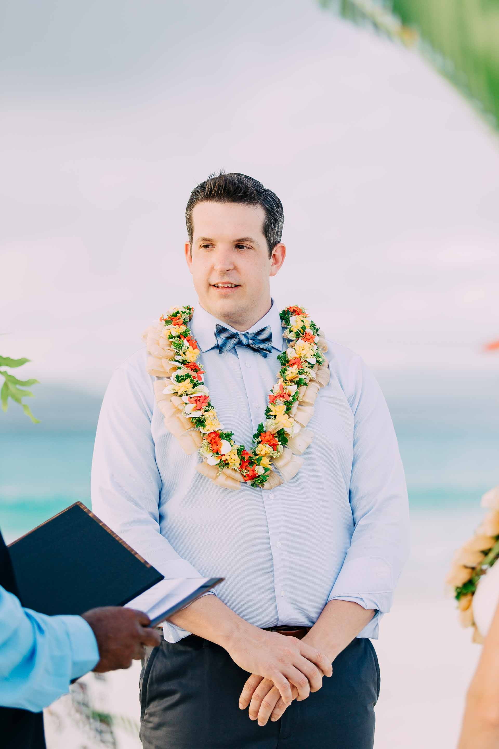 Emotional Groom says his vows during his Fiji elopement on a sand bar in the ocean.