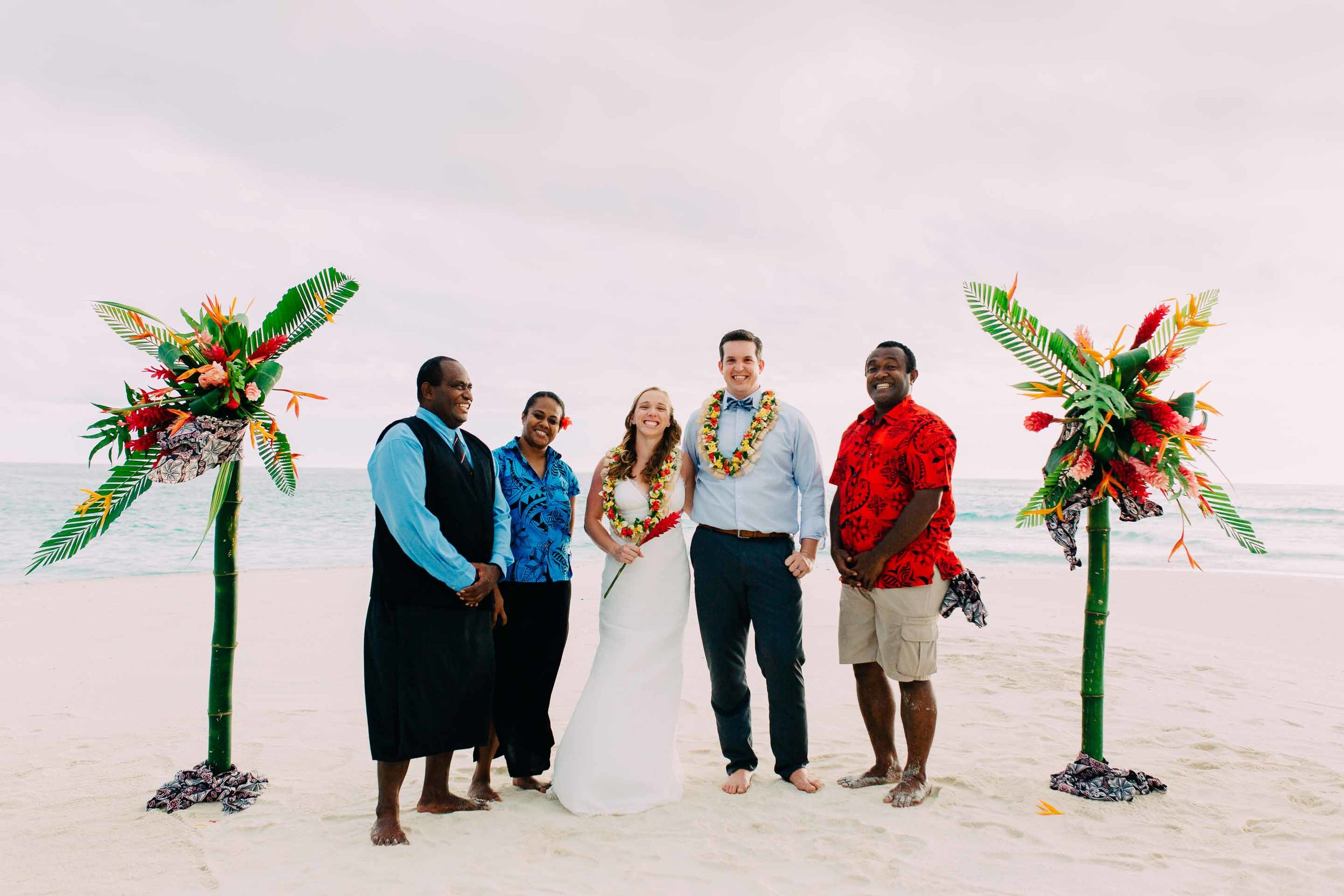 Royal Davui staff pose with the happy newlyweds on the sand quay after the ceremony.
