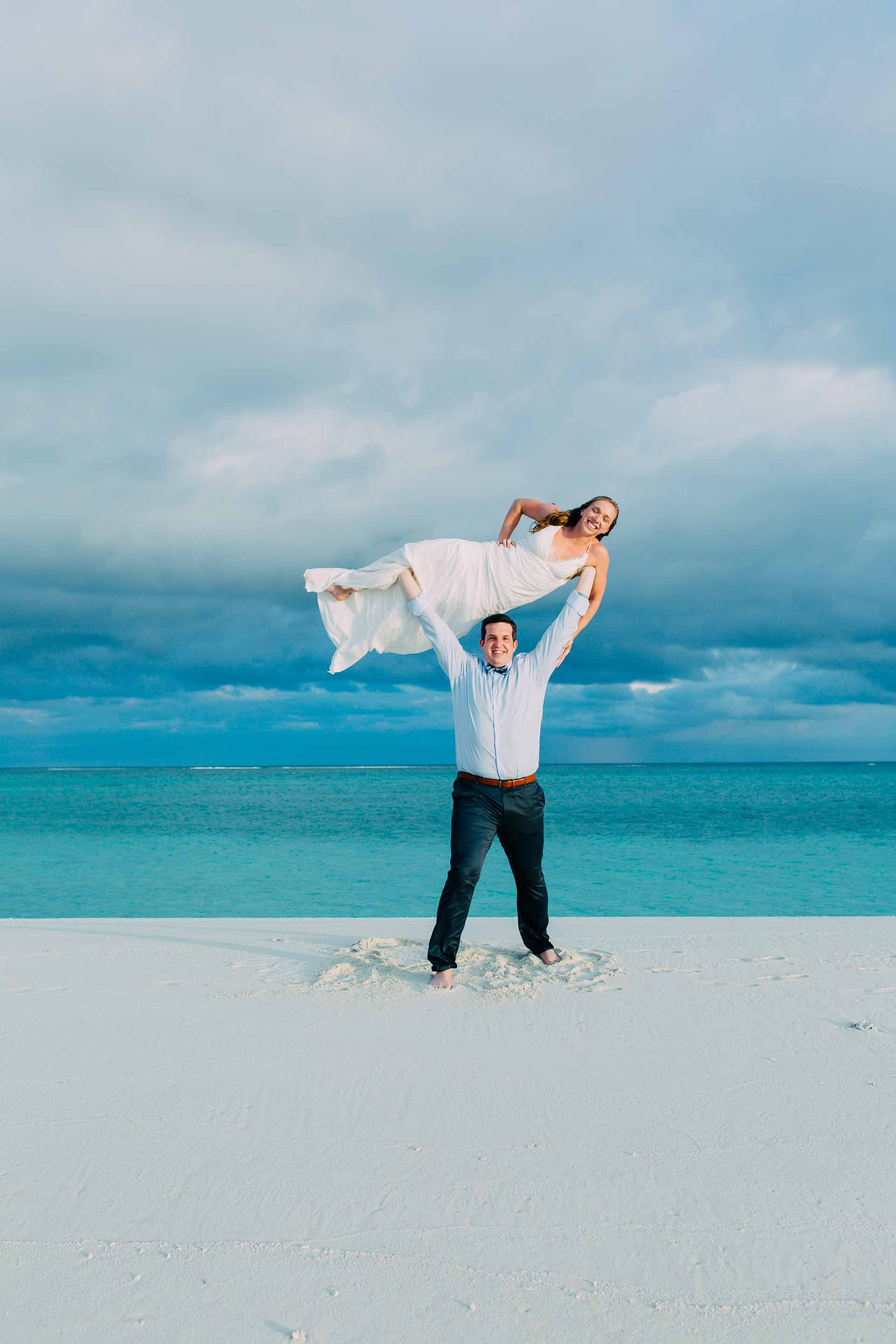 Gym junkies just married and no threshold heres the solution. Groom holds Bride over his head. Just married in paradise.