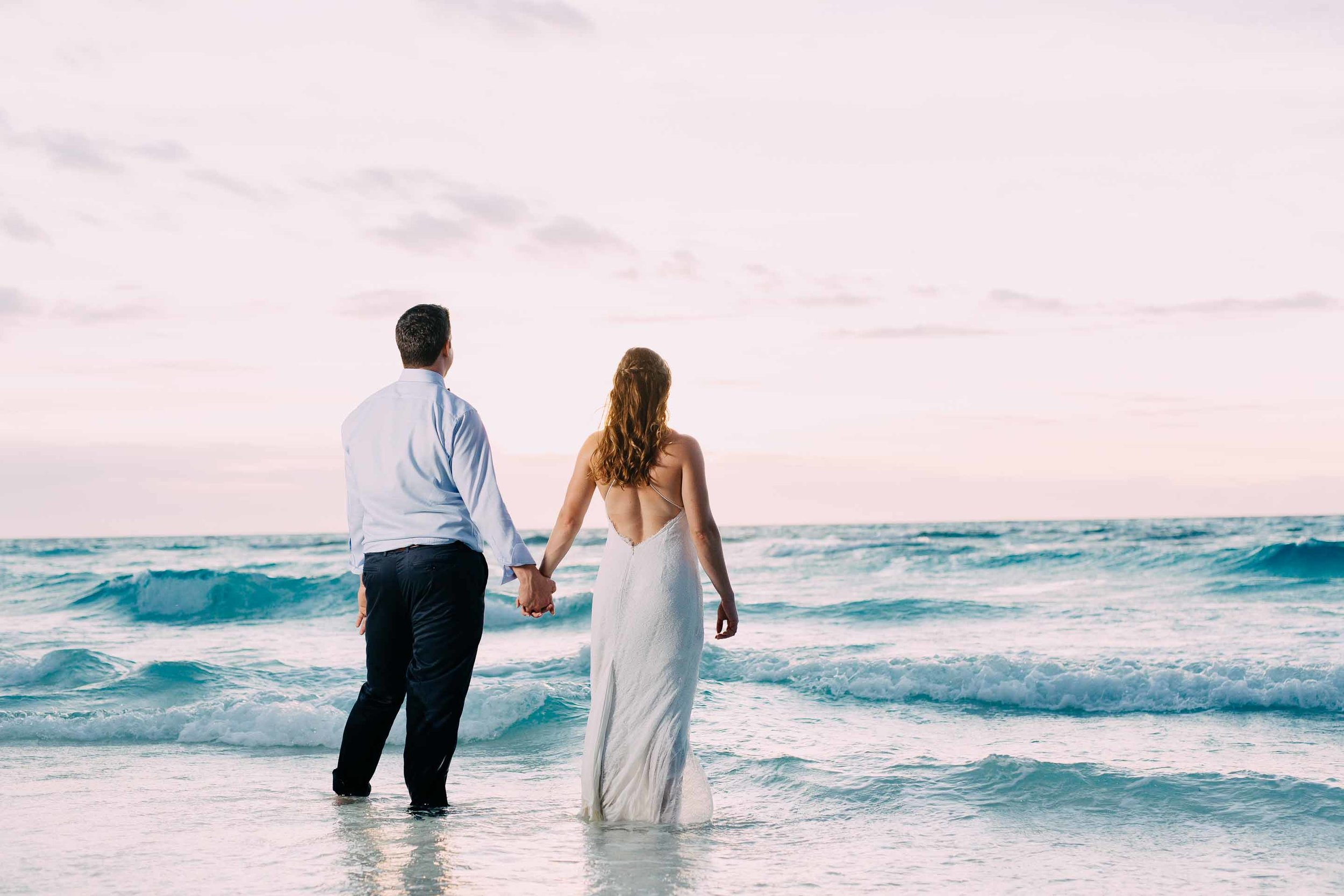 Newlyweds wade into the warm South Pacific Ocean moments after getting married on the sand quay.