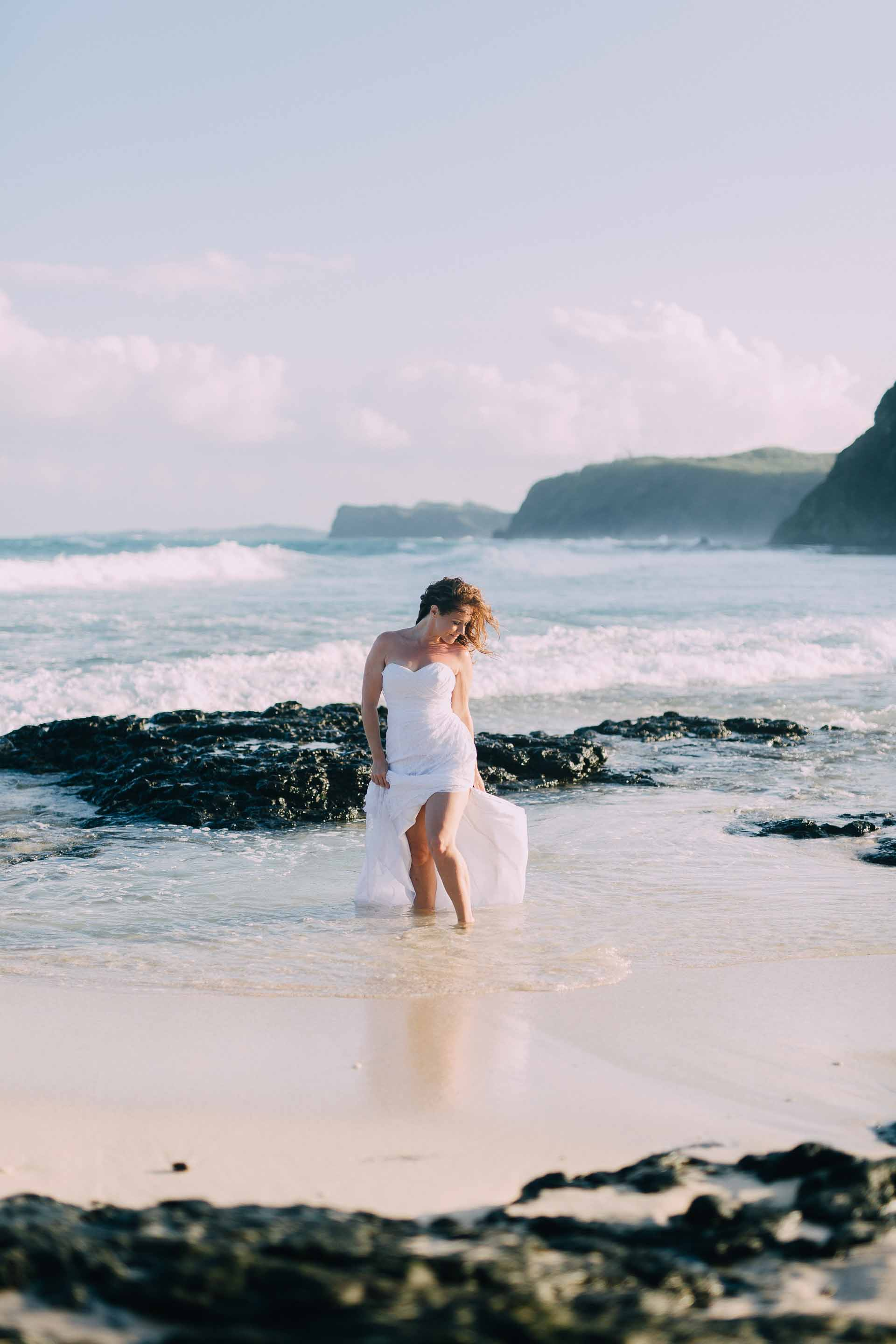 The bride in her wedding dress in the water