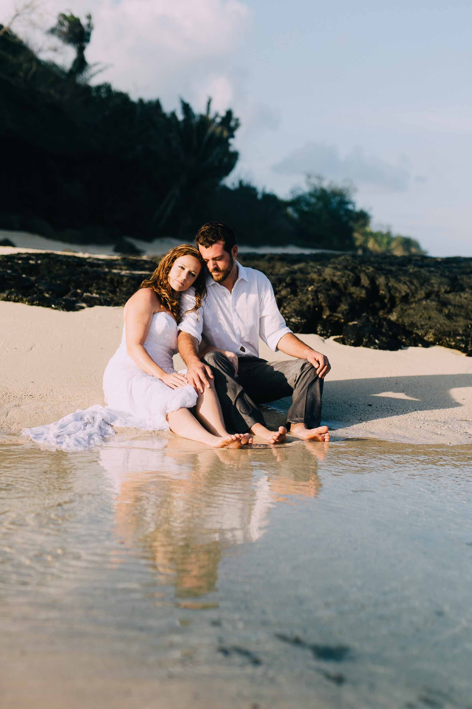 Newlyweds looking at camera as they sit on the beach, wet