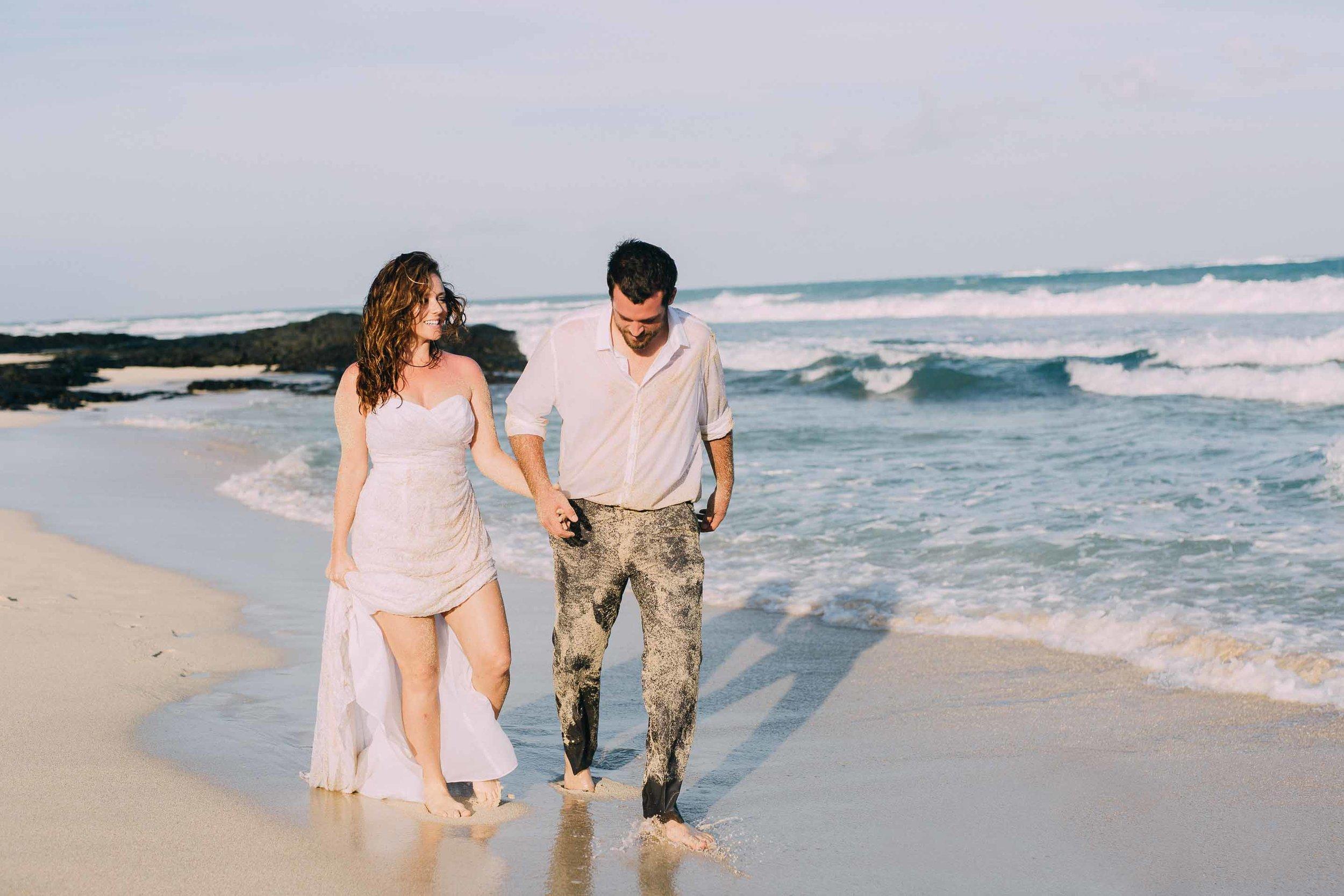 Recently married couple walk on beach in wedding attire