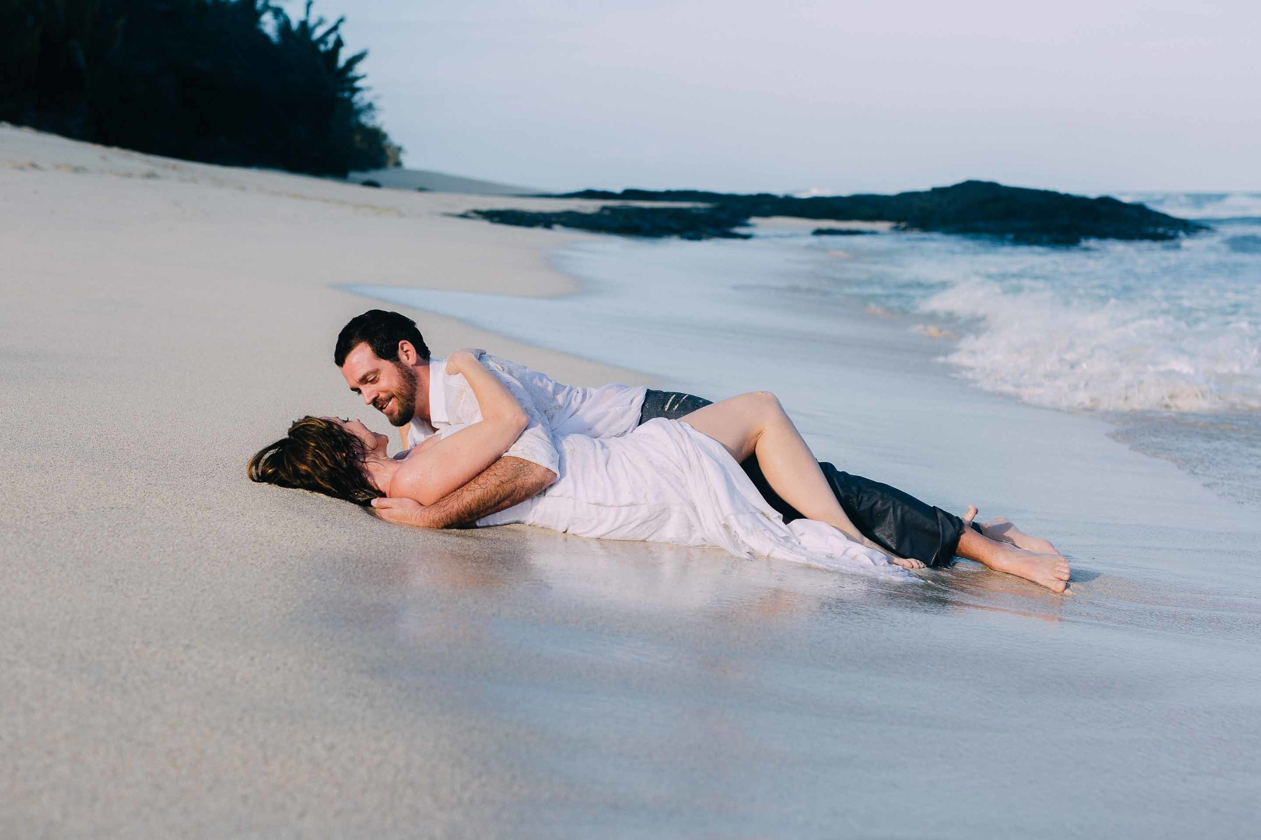 Newlywed couple in each others arms on the beach