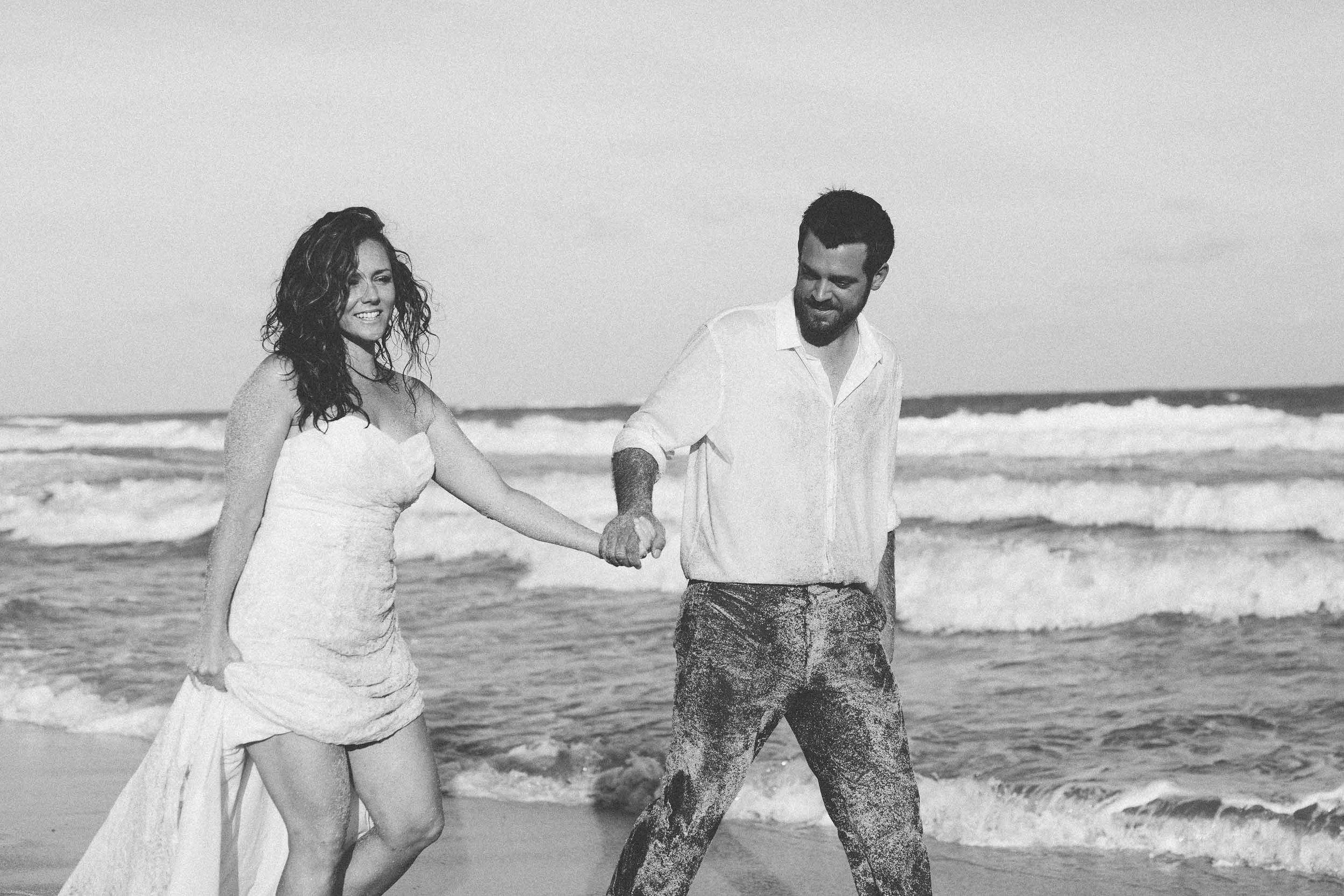 Black & white photo of newlywed couple walking along Lomalagi beach in Fiji for their trash the dress session