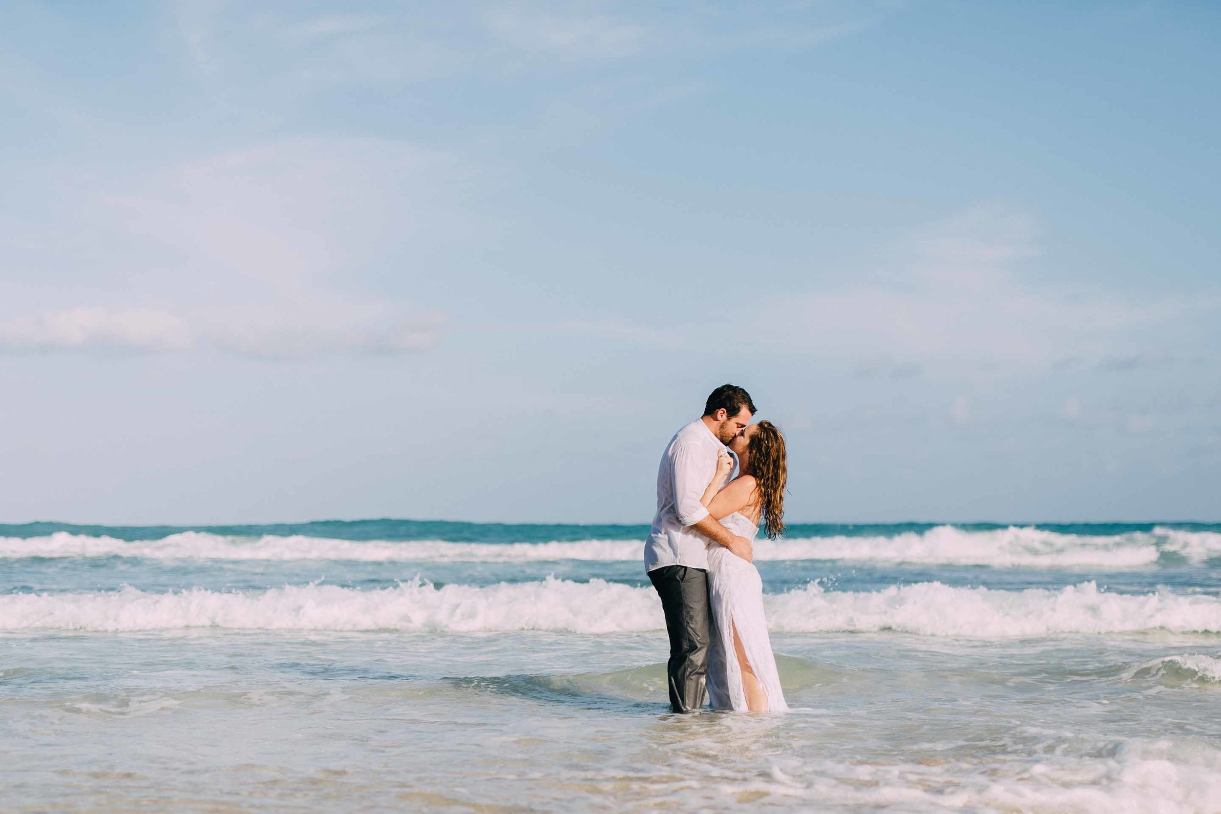 Newlyweds in shallow water, kissing