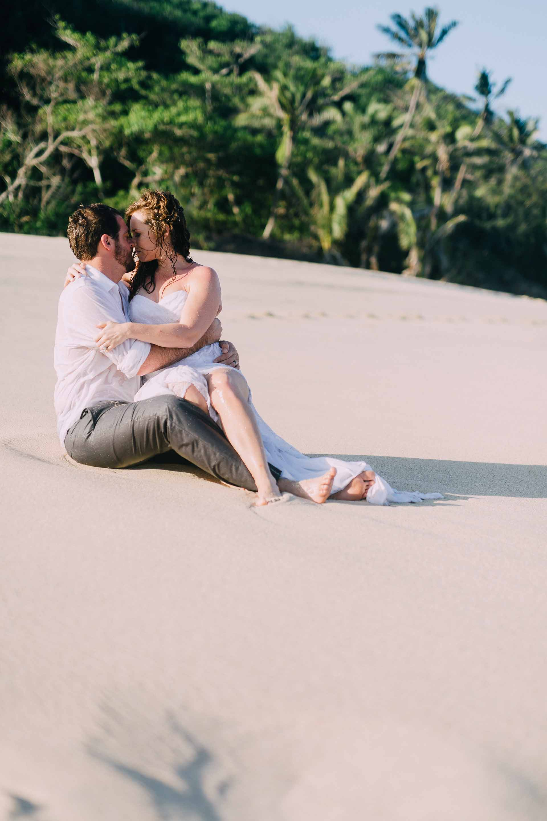 Bride and groom on the beach, kissing