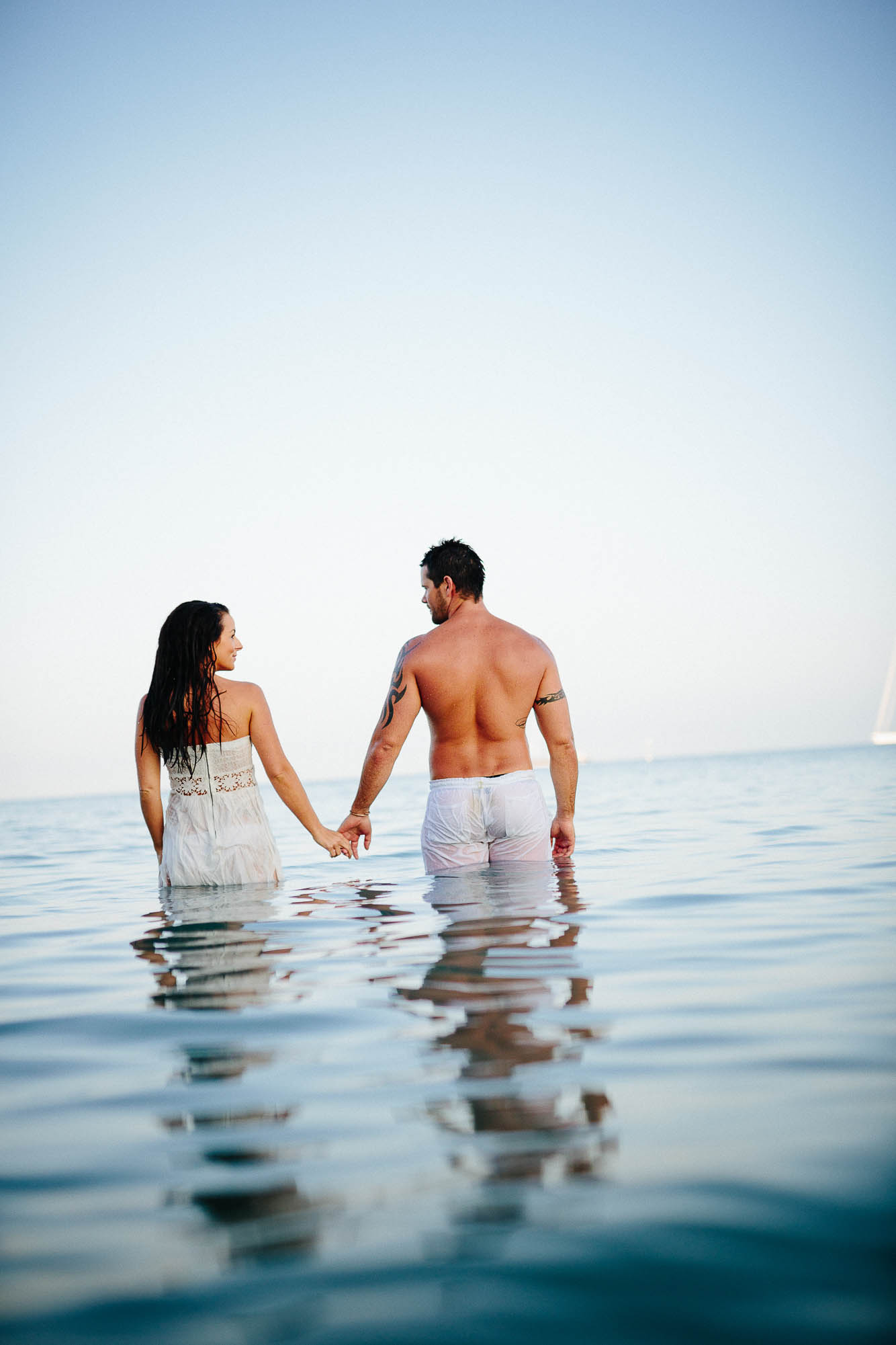 Couple standing in the shallow water for trash the dress session